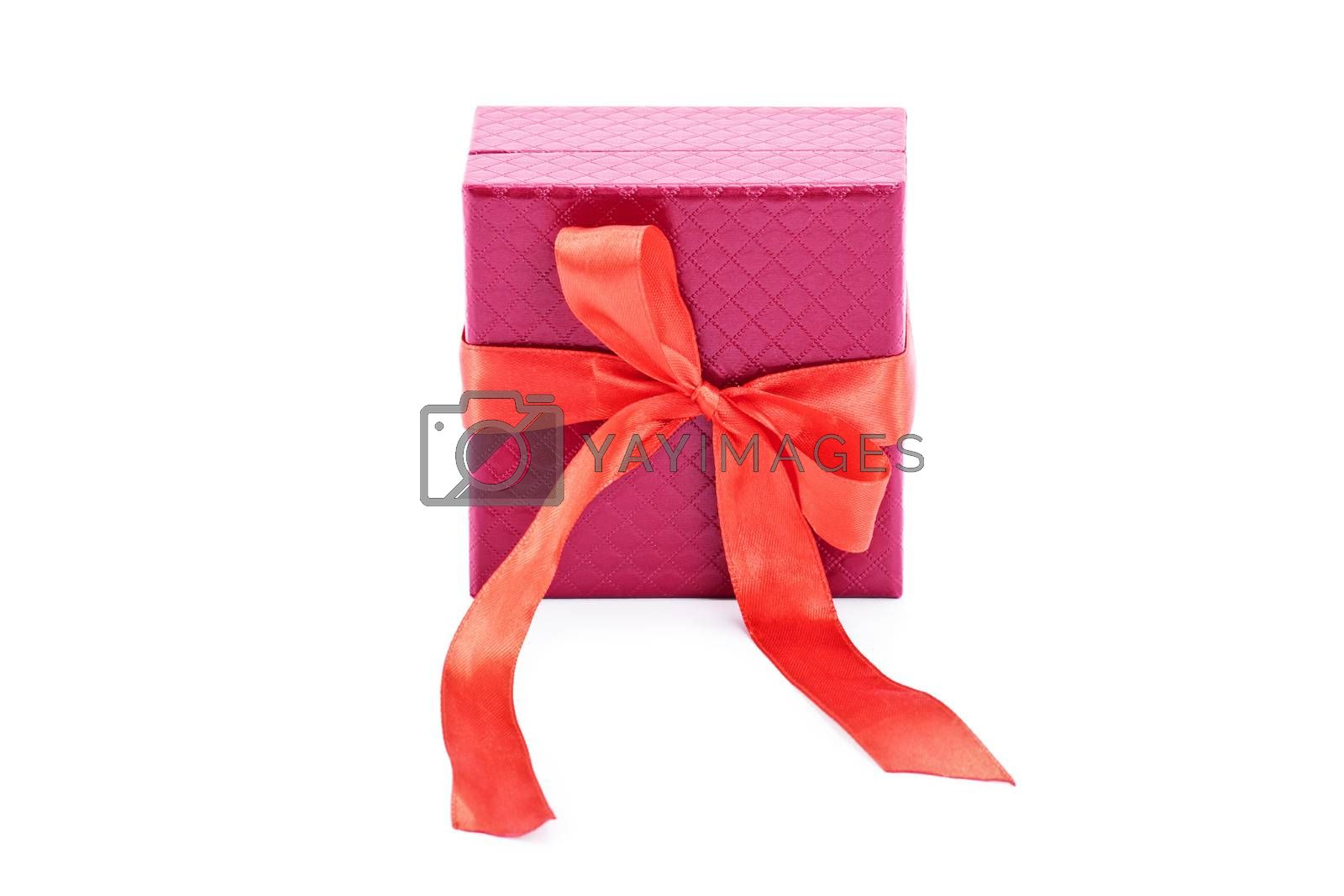 Close up of a red gift box and red bow ribbon, isolated on white background. Christmas, New Year, anniversary, birthday, Valentine's Day concept.