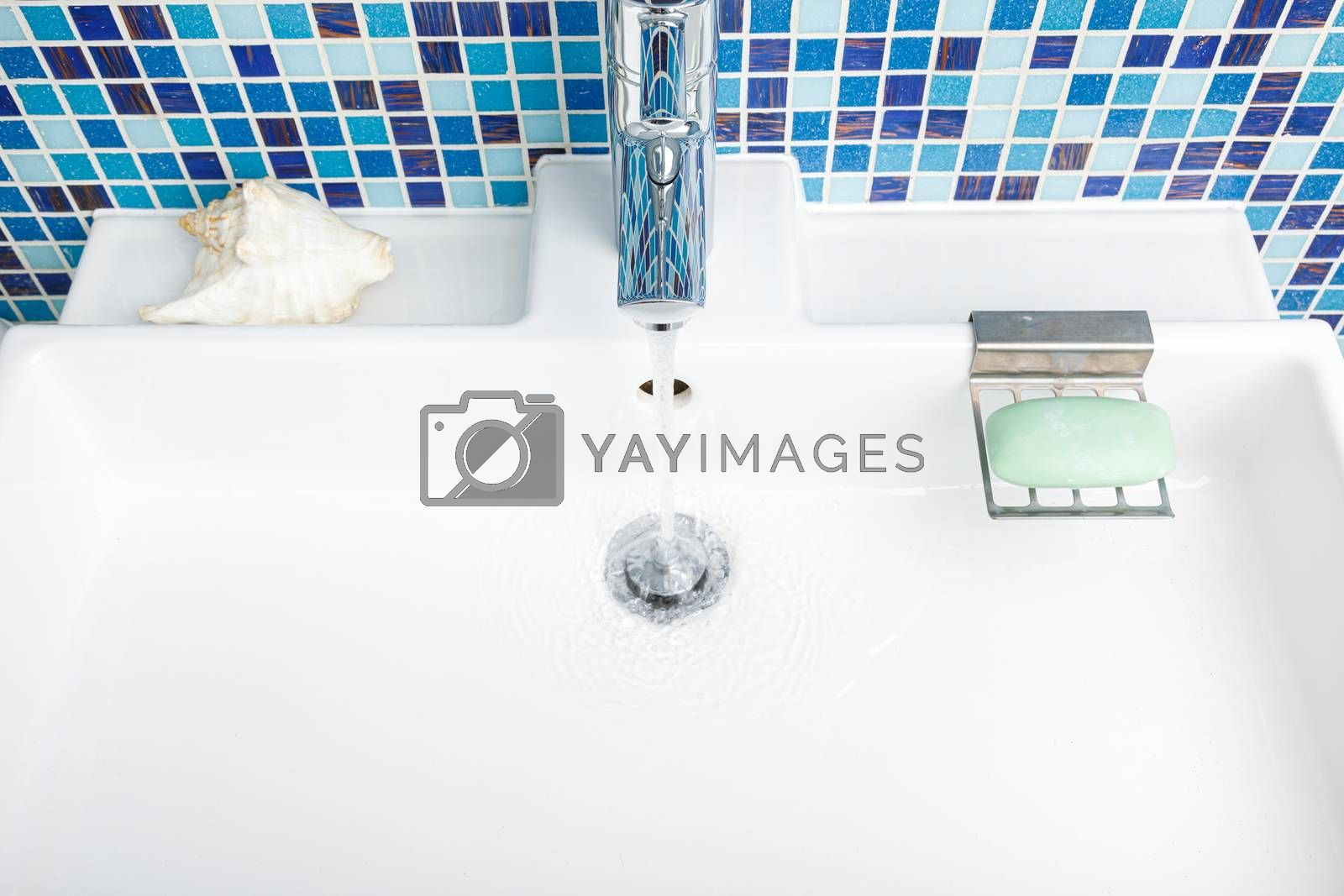 Bathroom sink tap with running water - wasting water concept