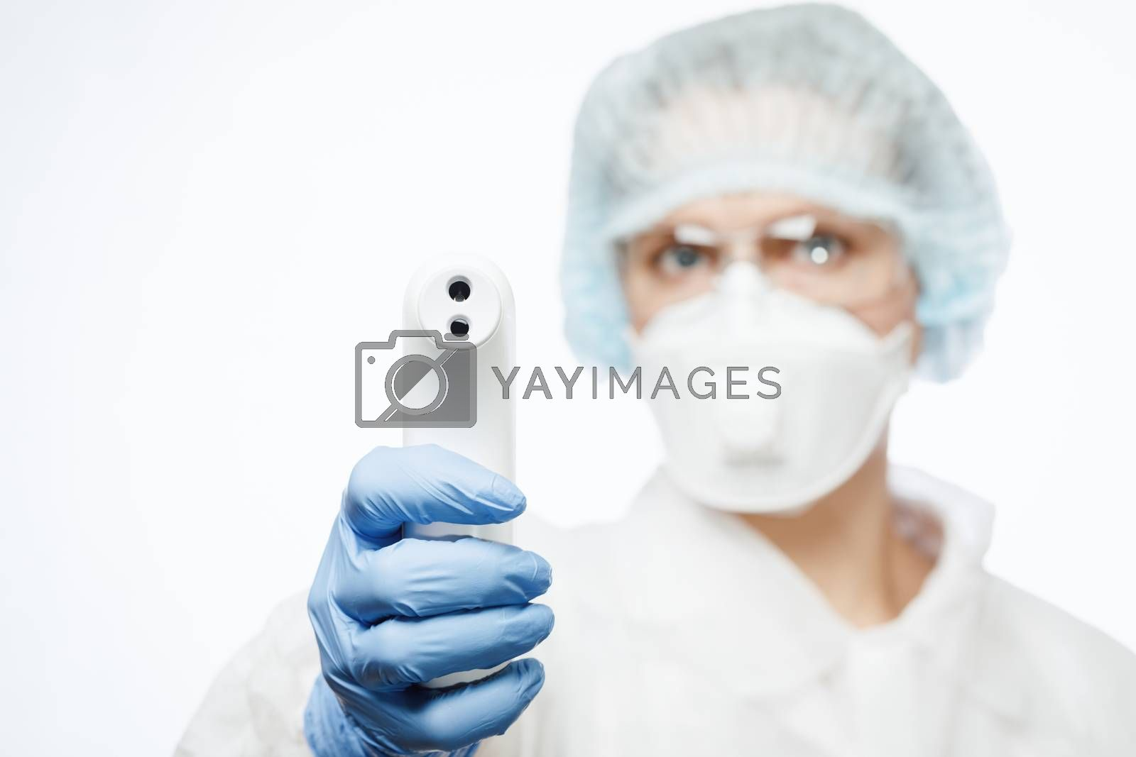 Close-up shot of doctor wearing PPE protective suit and surgical mask using infrared forehead thermometer or thermometer gun to check body temperature for virus symptoms - coronavirus outbreak concept
