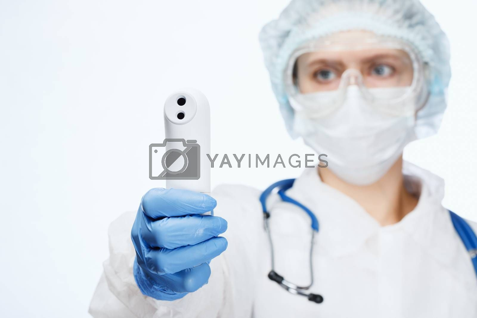 Close-up shot of doctor wearing protective suit and surgical mask using infrared forehead thermometer or thermometer gun to check body temperature for virus symptoms - coronavirus outbreak concept