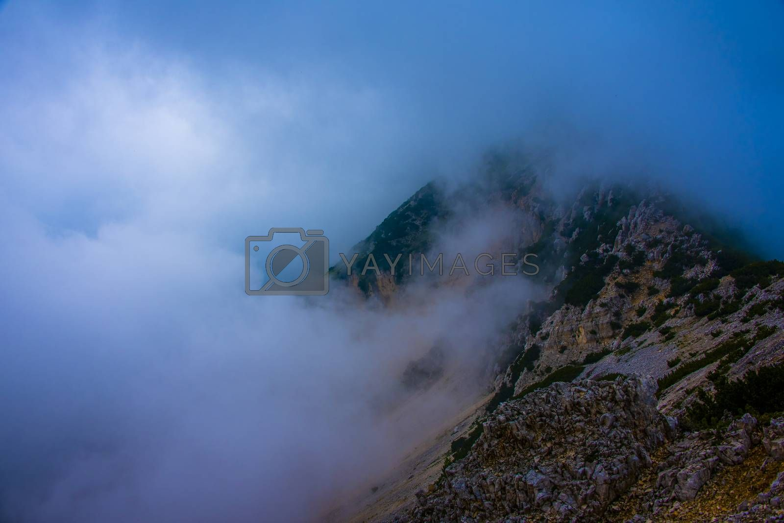 white clouds on the tops of the Venetian pre-Alps on the chain of Monte Baldo on Lake Garda, Malcesine, Verona, Italy