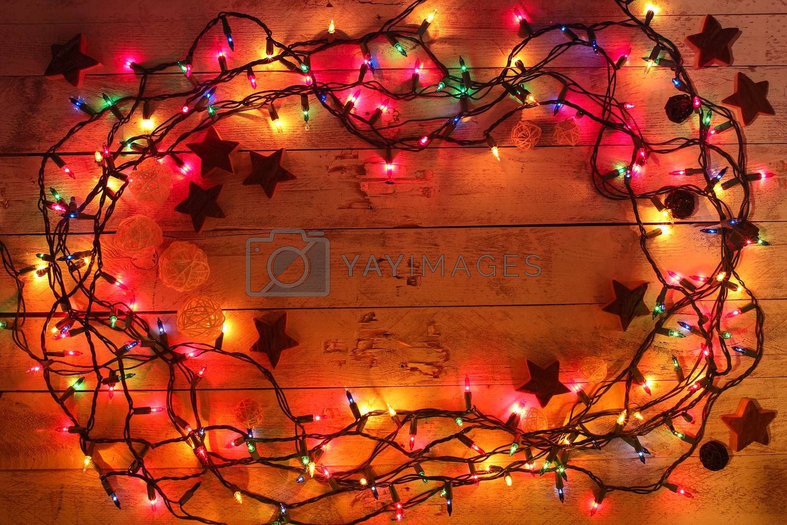 Glowing colorful Christmas lights on wooden background. Christmas wooden decor. Garland. New Year. Flat lay, top view, copy space.