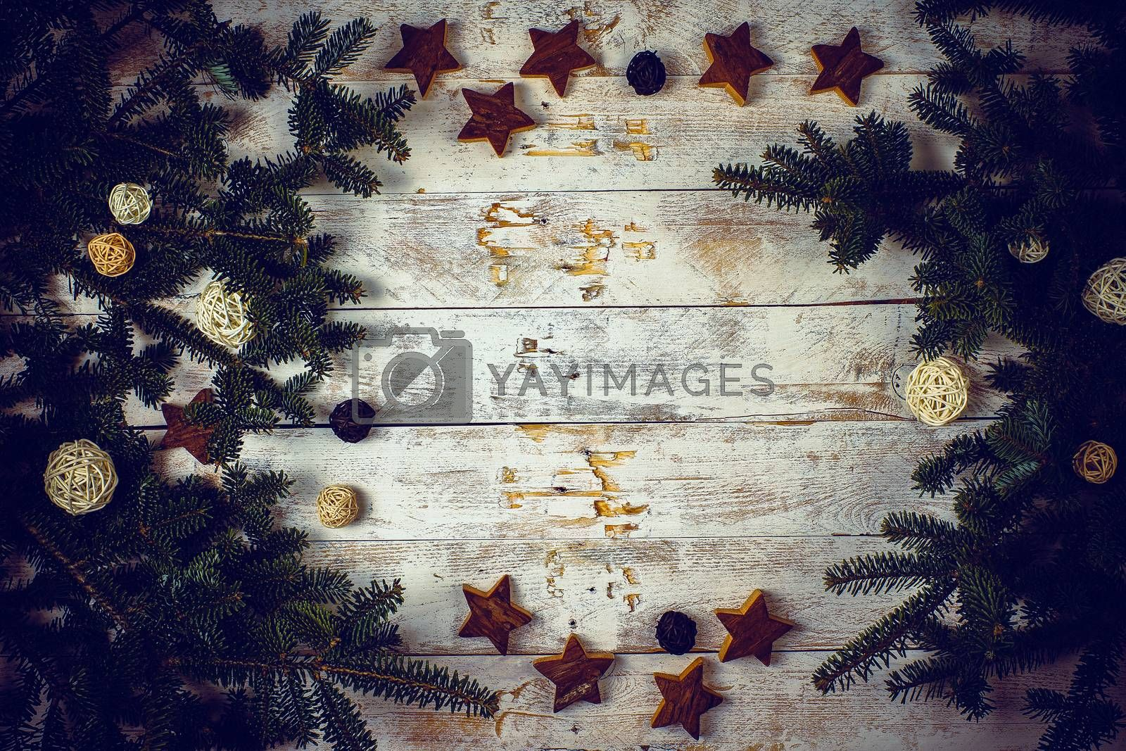 Christmas composition. Frame made of fir tree branches with decoration on rustic wooden background. Flat lay, top view, copy space.