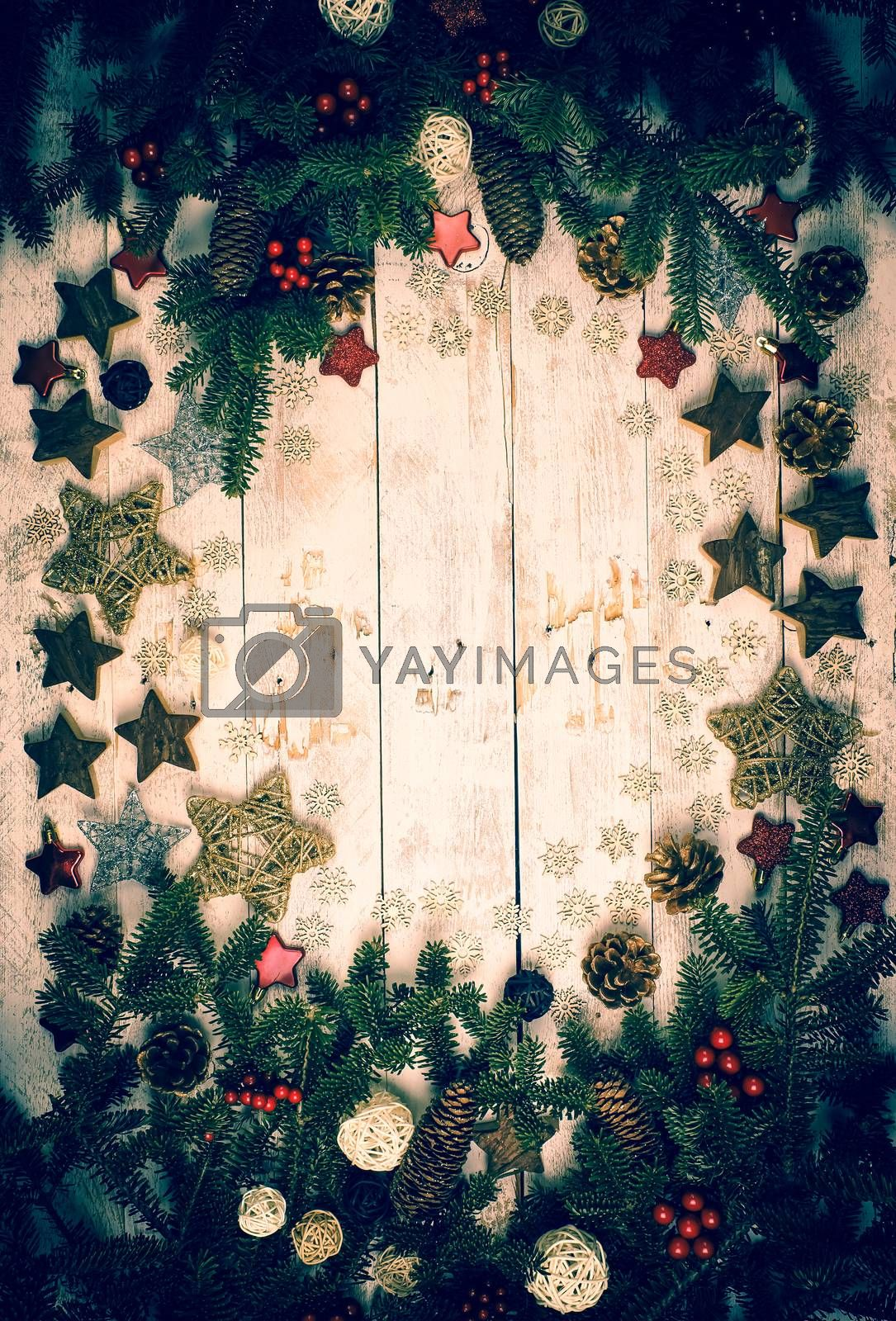 Christmas background. Frame made with fir twigs, red berries, cones and Xmas decoration on a wooden board in vintage style. Flat lay, top view, copy space.