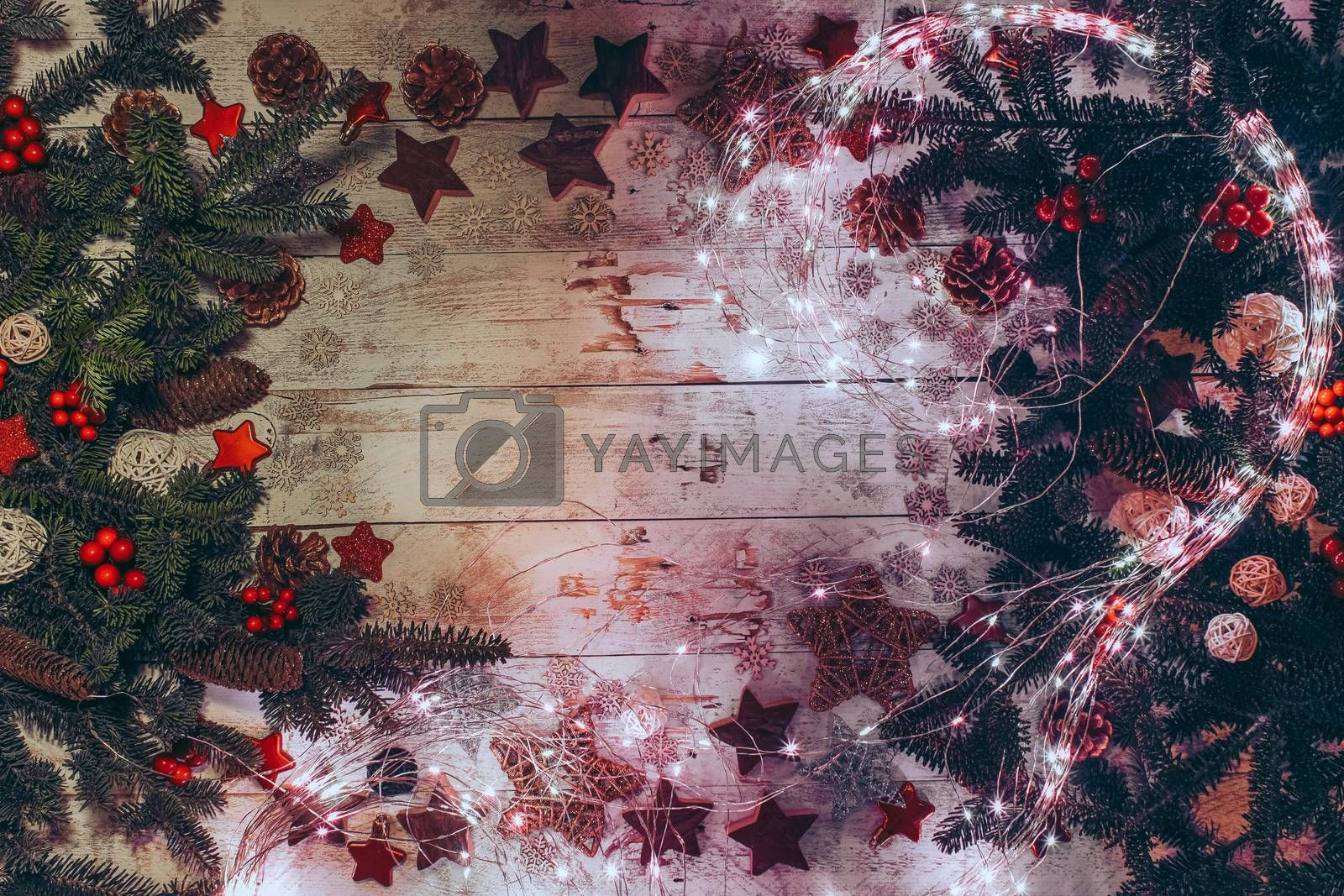 Christmas background with fir twigs, red berries, cones and Xmas decoration, lights on a wooden board in vintage style. Flat lay, top view.