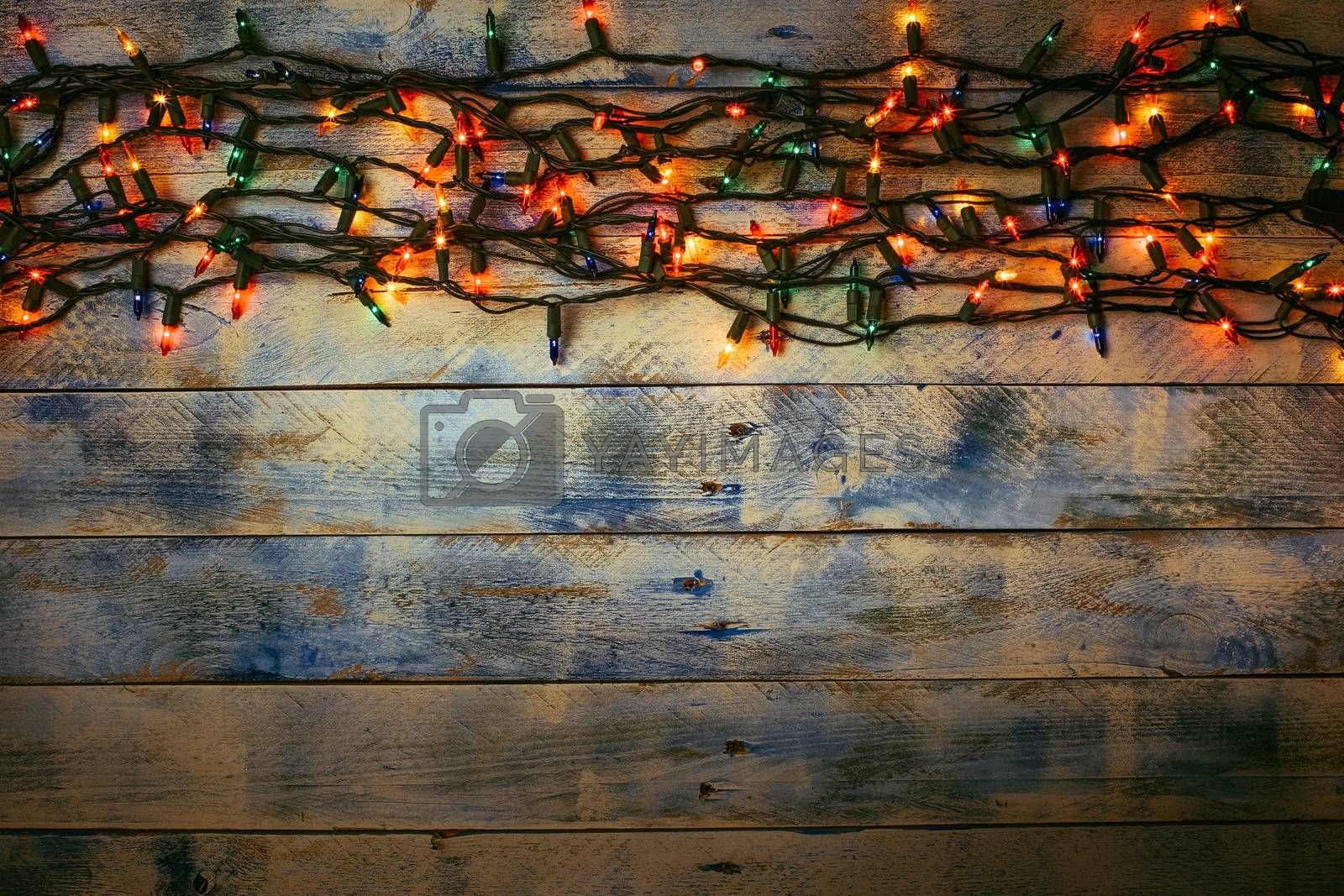 Christmas lights over white and blue painted planks for background. Christmas light decorations on wood texture. Flat lay, top view, copy space. Garland.