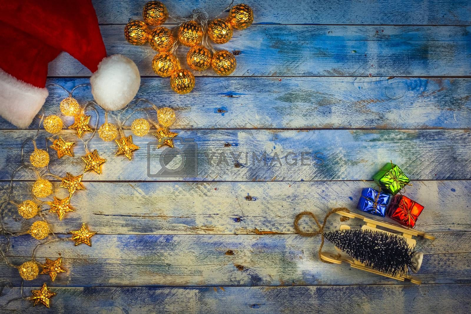 Christmas background with santa hat and christmas lights with decoration on rustic vintage wooden background. Flat lay, top view, copy space.