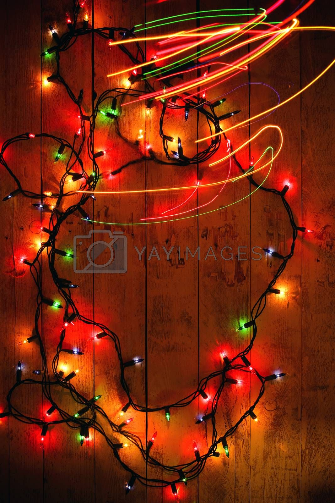 Colorful Christmas garland warm lights. Multicolored light lines. Wooden background. Long exposure. Top view. Vertical shot. Copy space.