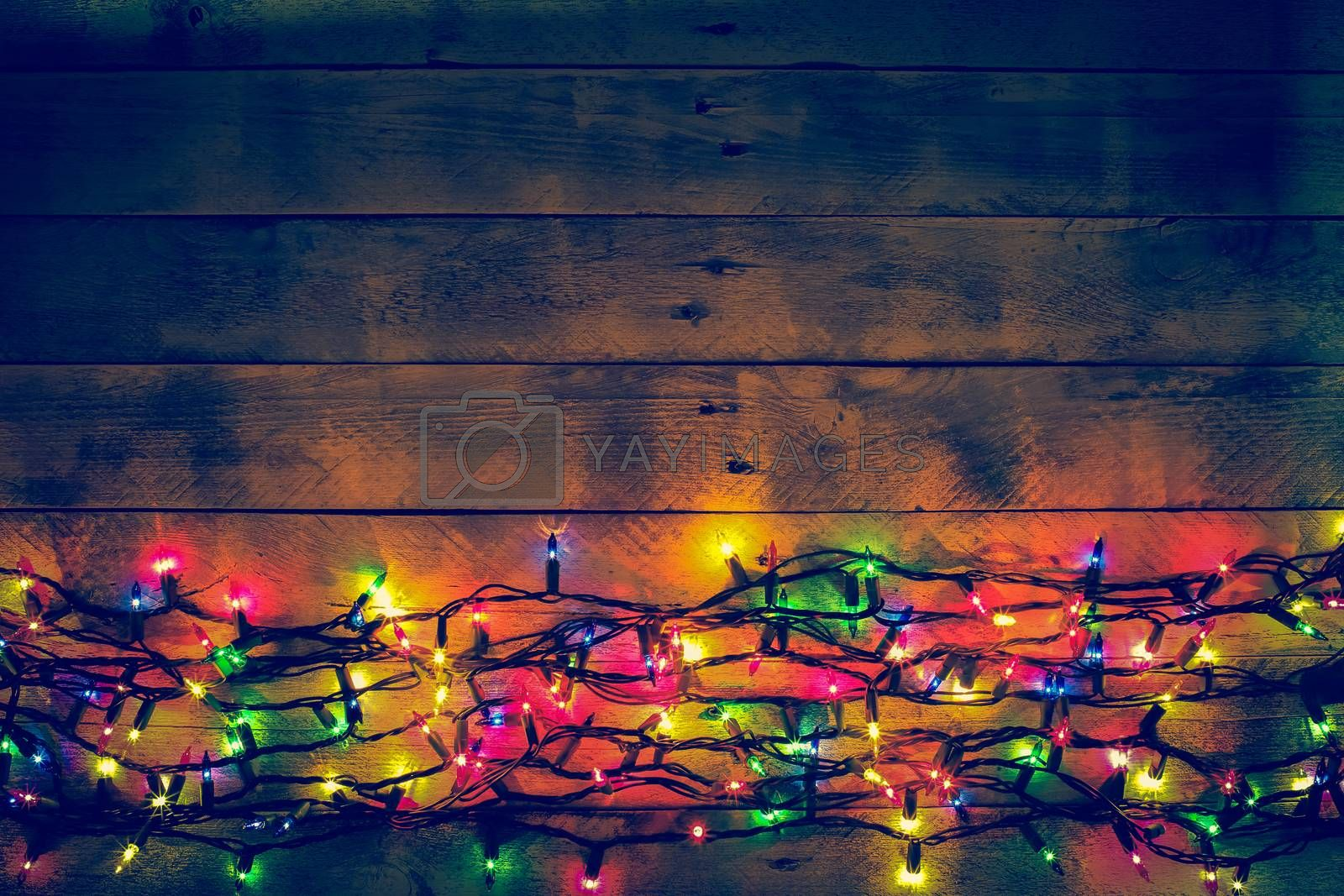 Colorful Christmas garland warm lights. Multicolored lights. Wooden background. Long exposure. Top view. Horizontal shot. Copy space.
