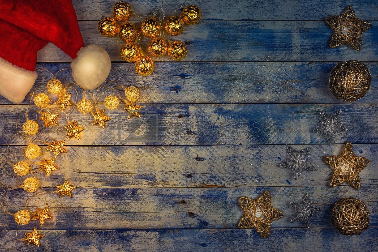 Christmas background with santa hat and christmas lights on rustic vintage wooden background. Garland. Flat lay, top view, copy space. Horizontal shot.