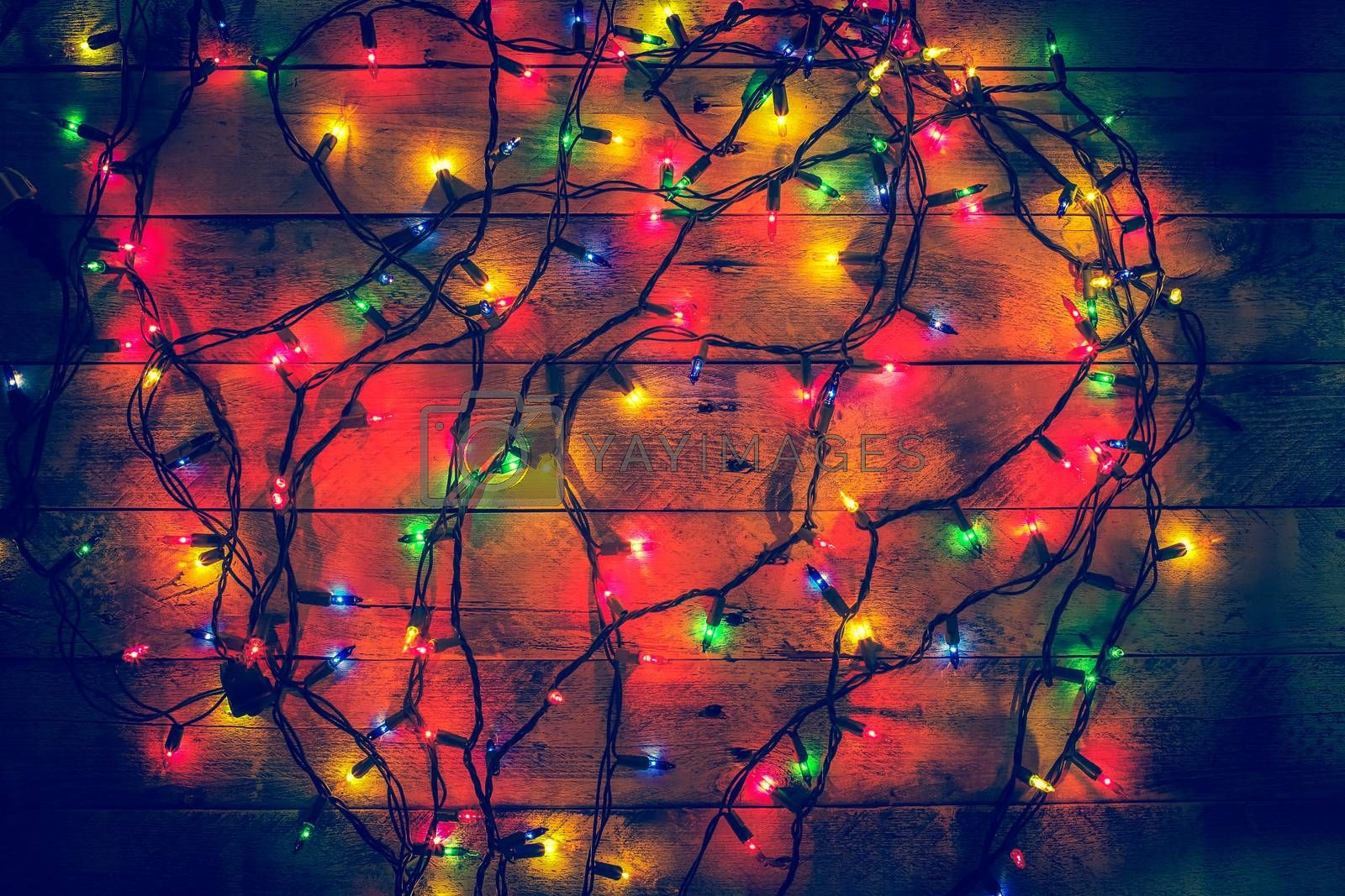 Glowing colorful Christmas lights on a wooden background. Christmas decor. Garland. New Year. Flat lay, top view, copy space.
