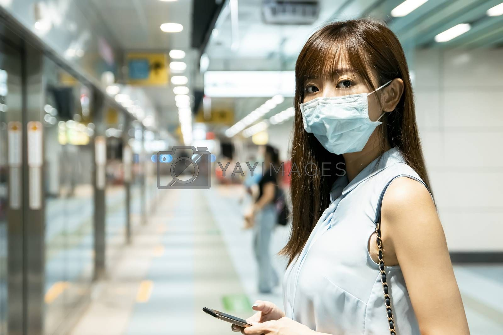 business woman wearing face mask at train station using the mobile phone