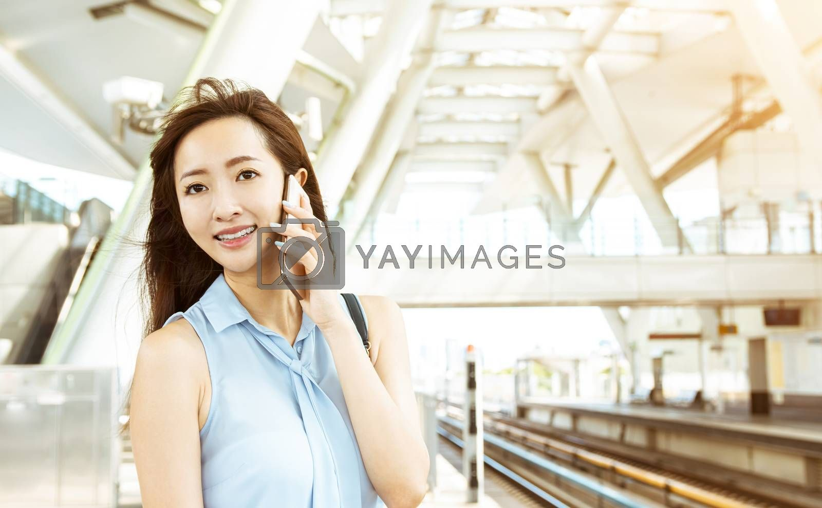 young woman talking on the phone in  train station