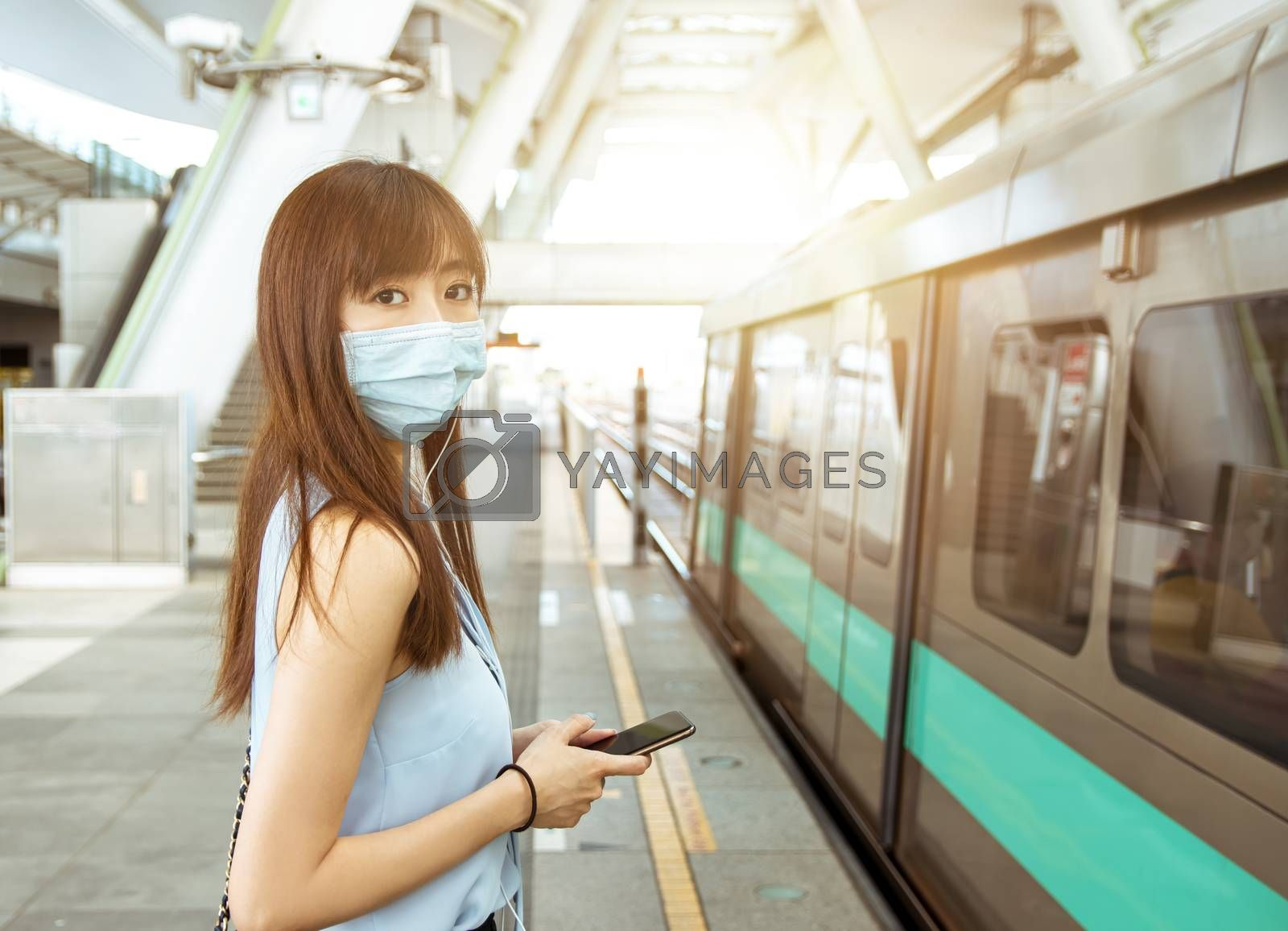 business woman wearing face mask at train station holding the mobile phone