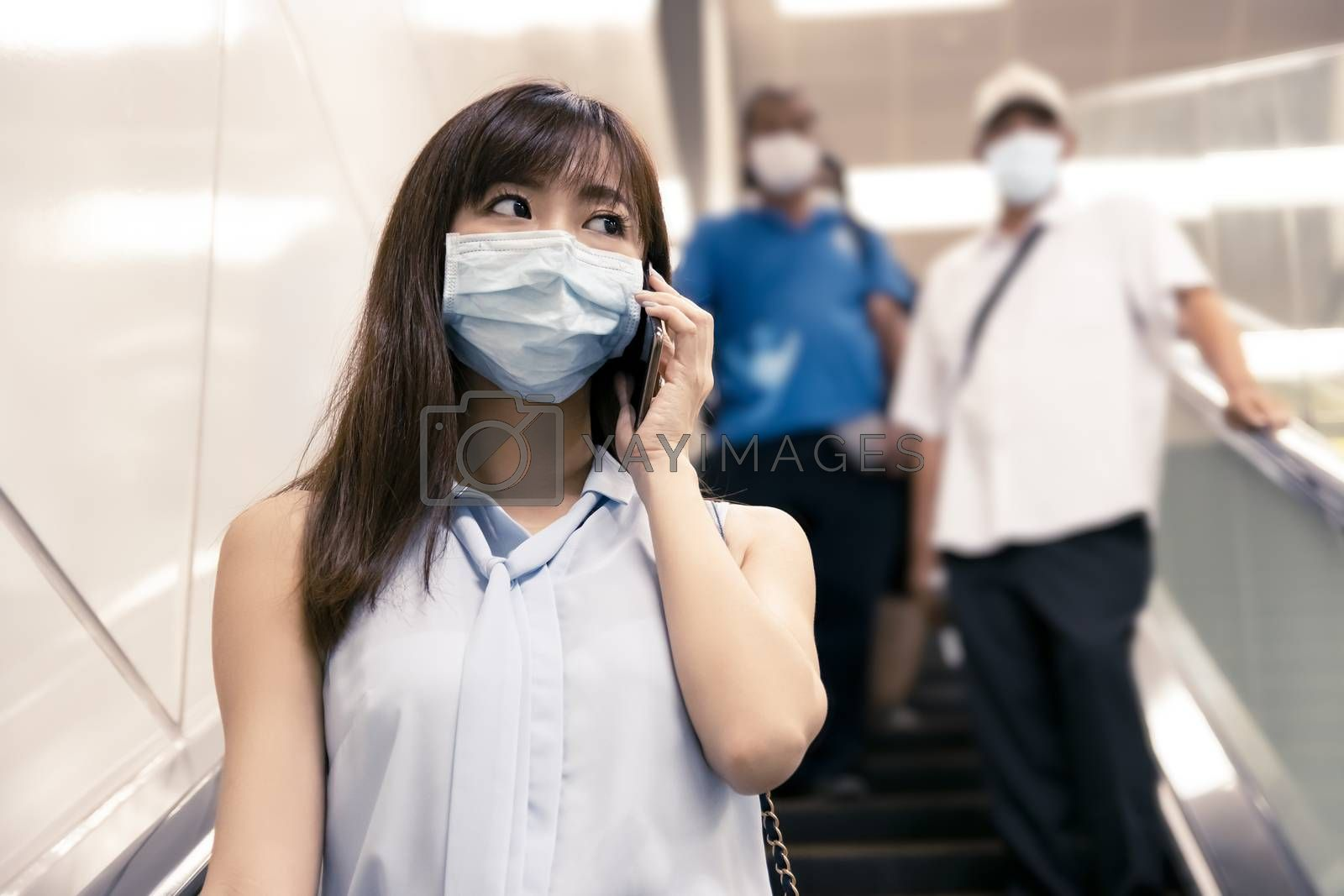 business woman wearing face mask at train station and talking on the phone