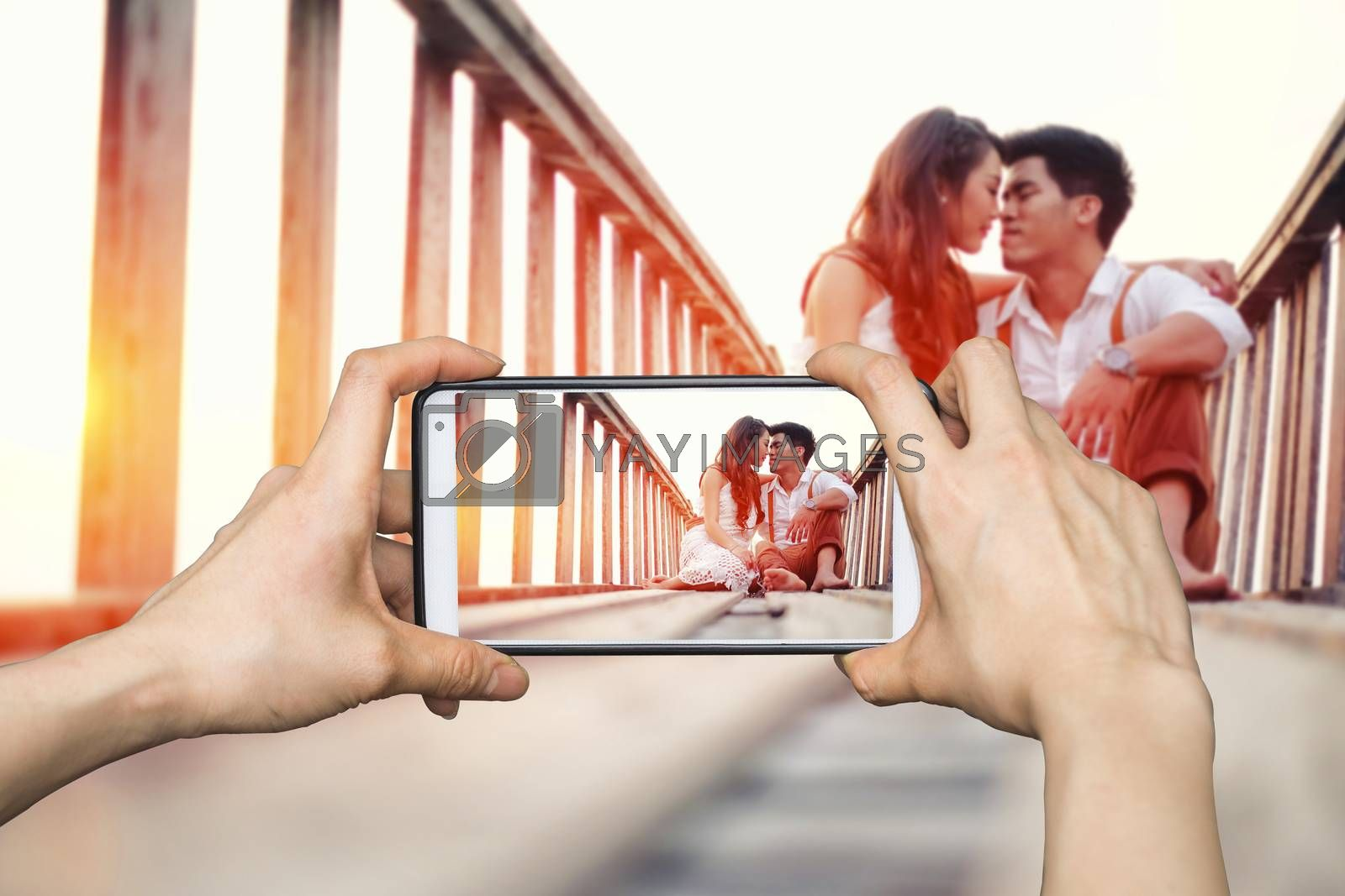 Girl taking pictures on mobile smart phone Happy couple relaxing in sunset