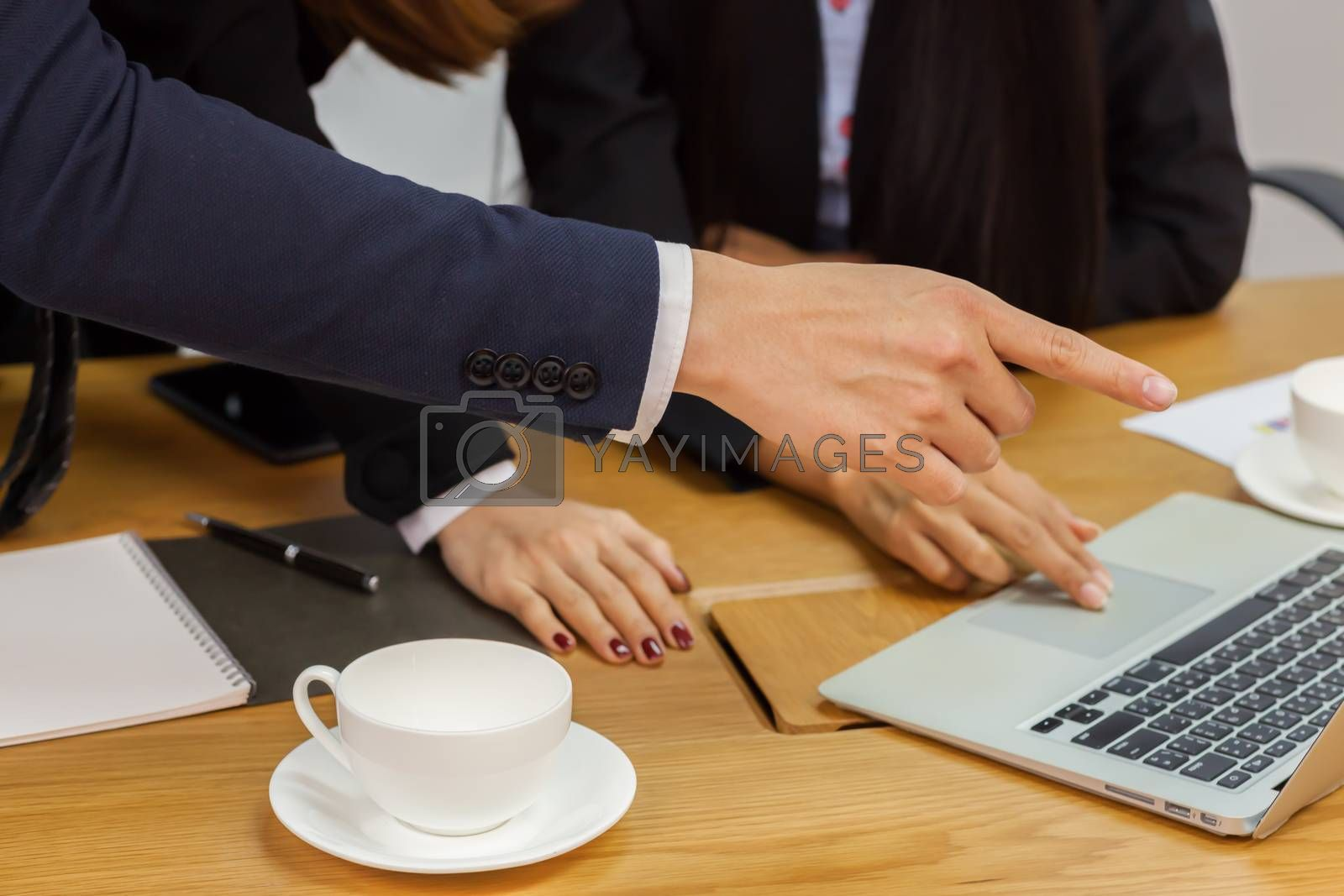 A business group discussion in meeting room with document and computer put on wooden table.