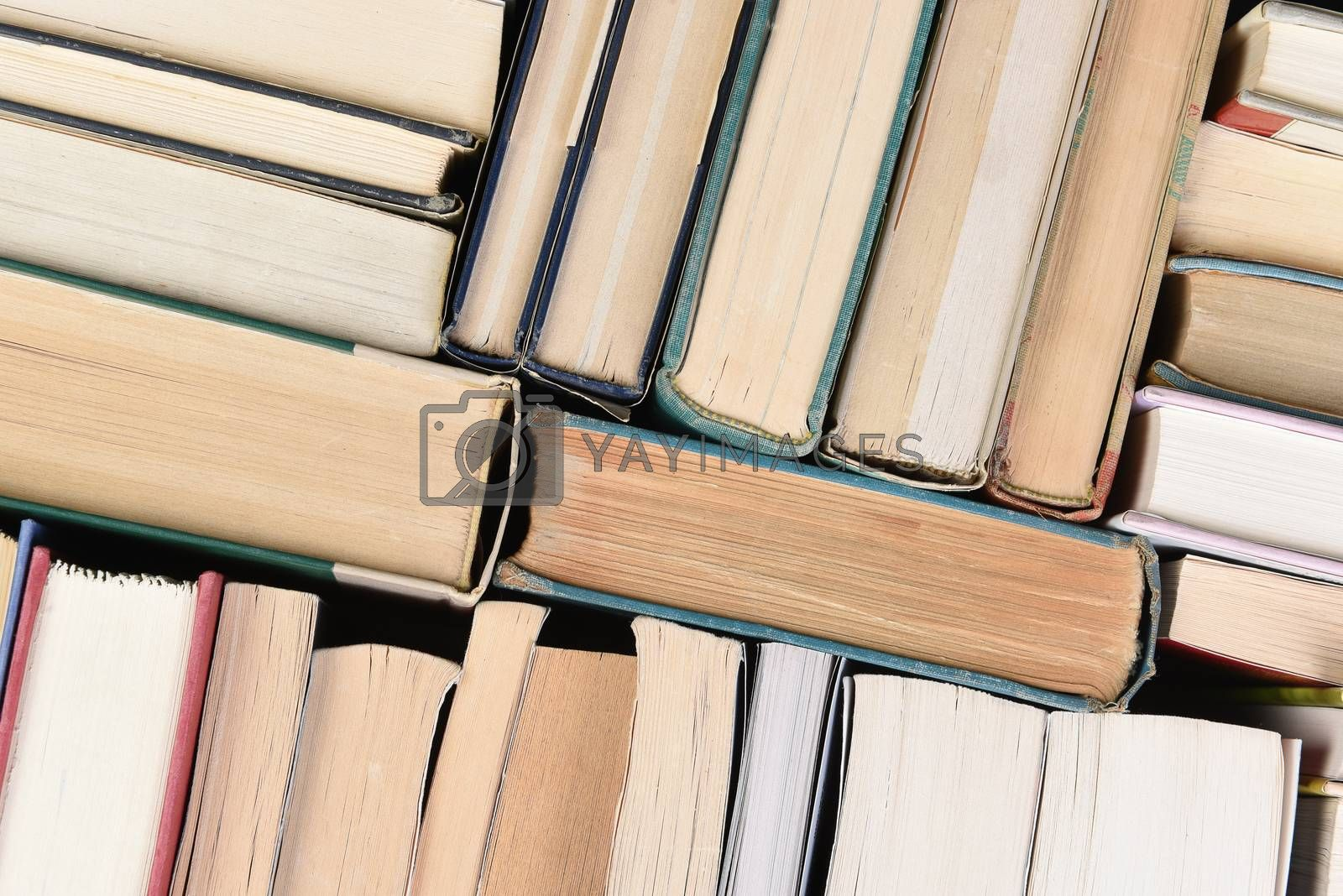 Closeup of a large group of used books in random order seen from directly above.