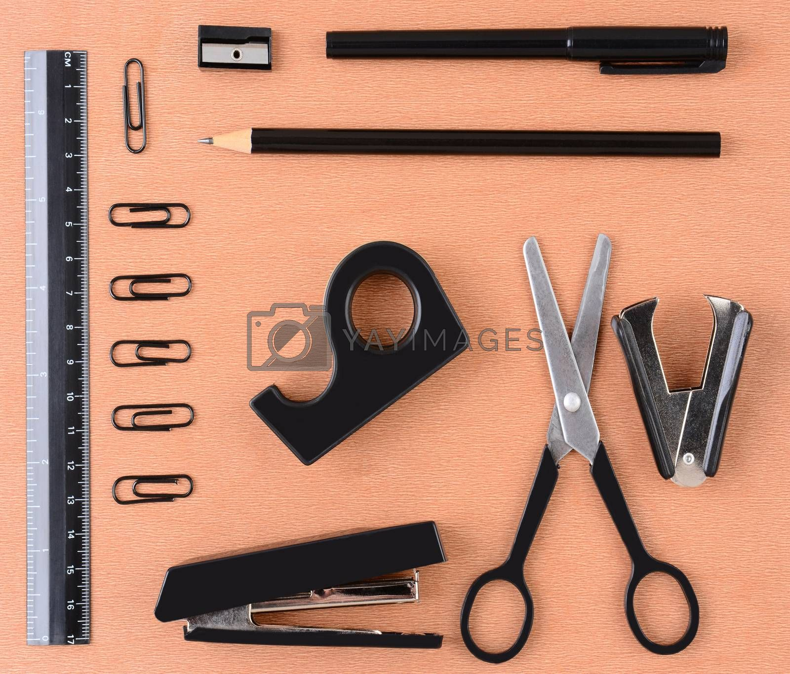 School or Office Supplies on a wood desk top. Square format showing various items that are all black in color.