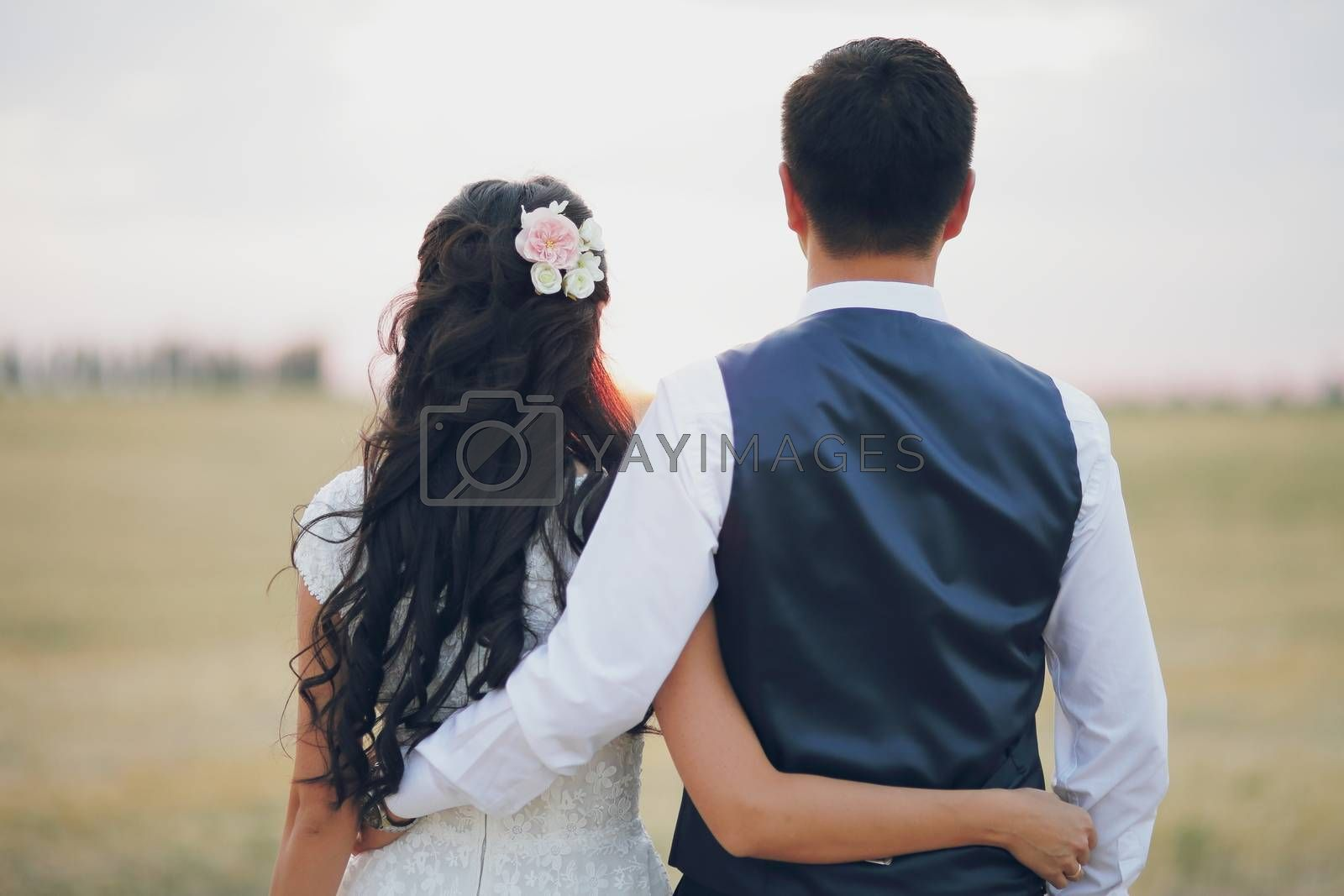 Wedding. Bride and groom hold hands and meet the sunset. A beautiful couple. High quality photo