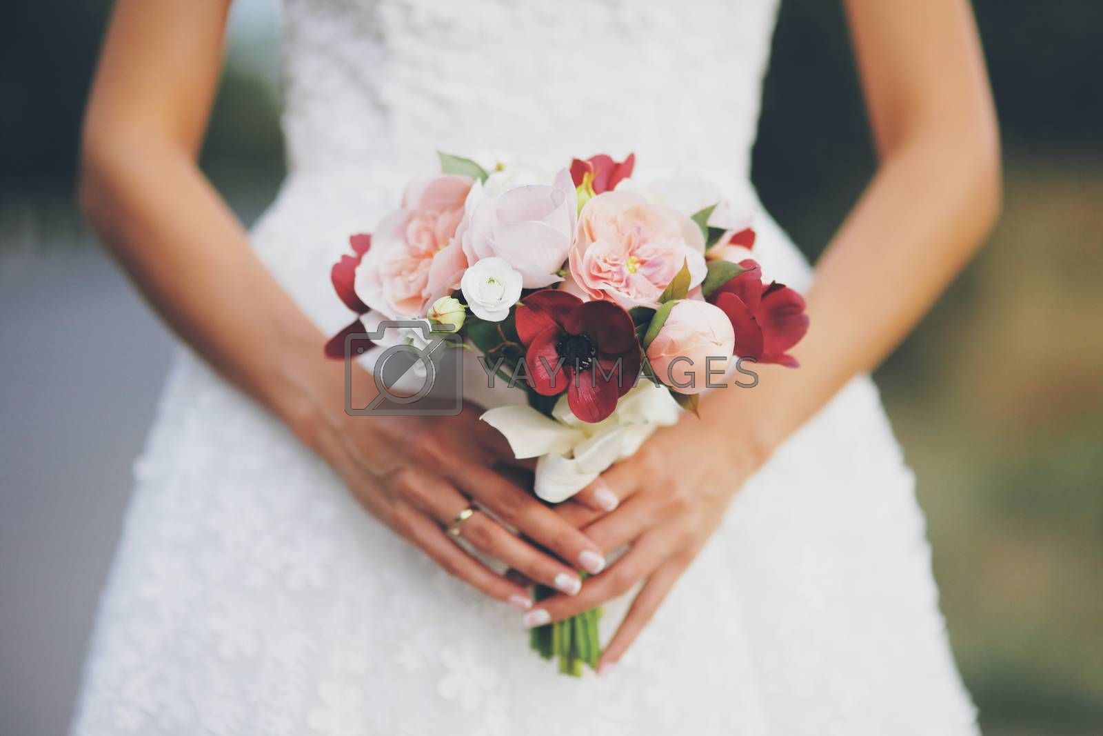 The bride holds a wedding bouquet. Women's hands with flowers. Wedding. A beautiful couple. High quality photo