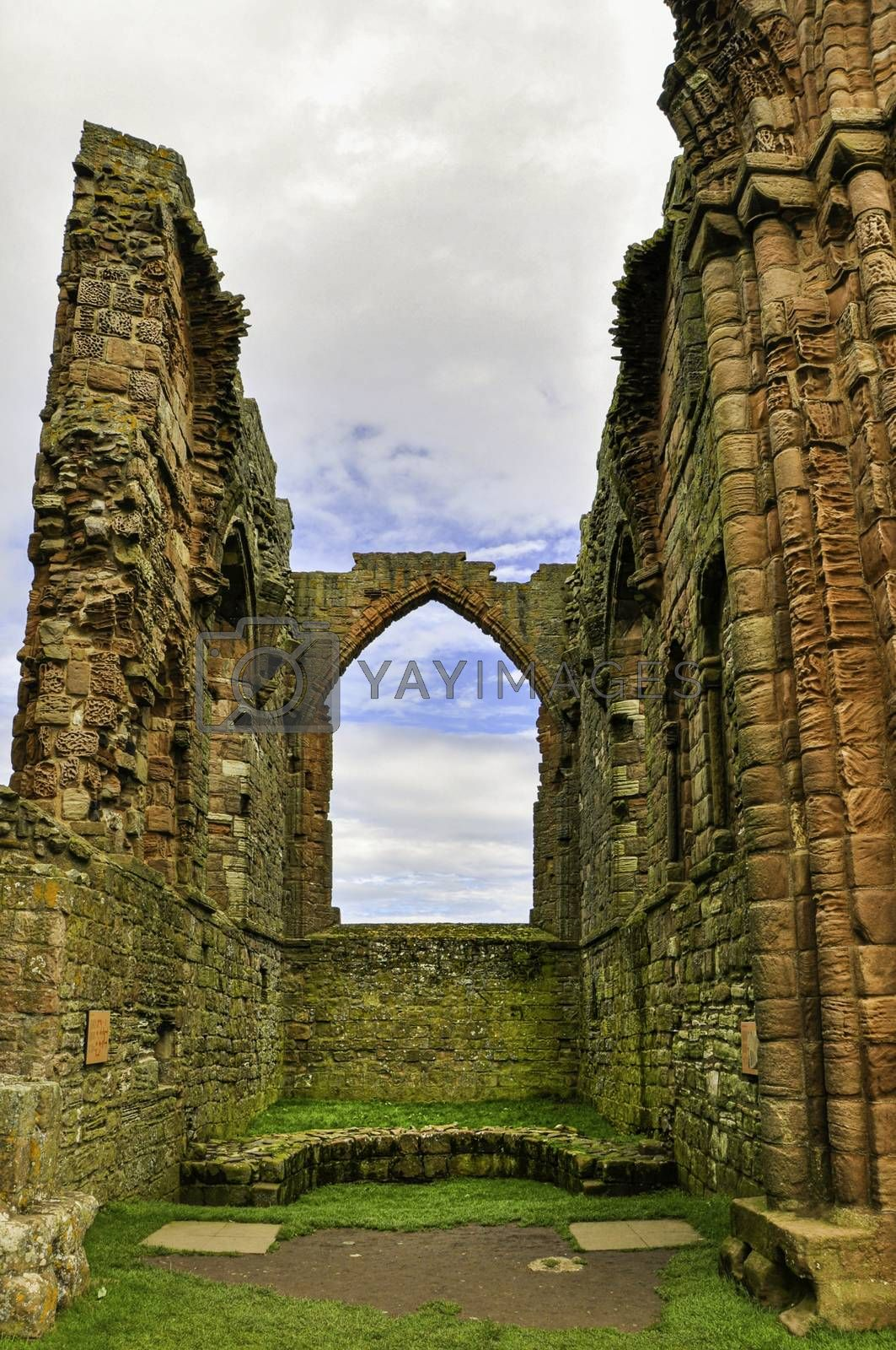 Derelict archway of a ruined old sandstone castle in the United Kingdom.