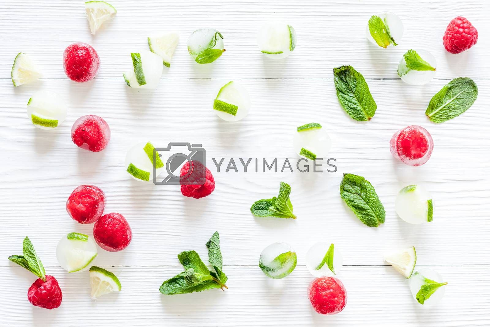Berries frozen in ice cubes background flat lay.
