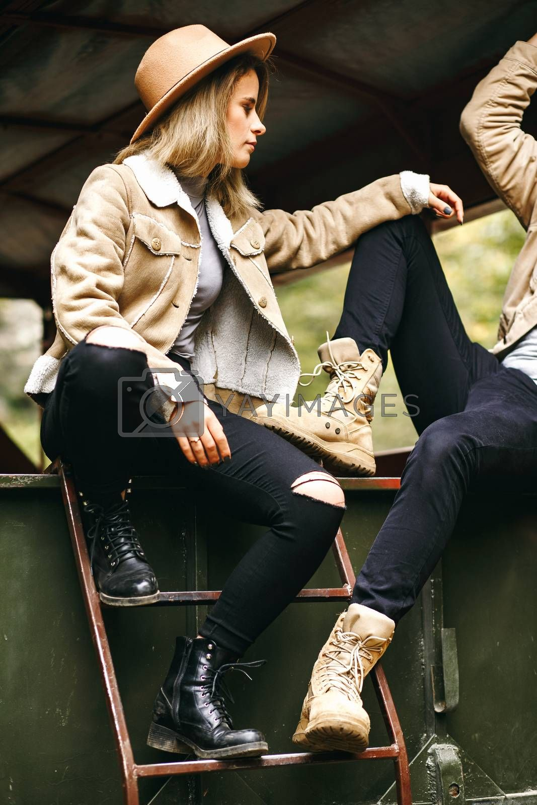 A beautiful girl and a handsome man in military truck. Lovestory. Military vehicle. Military fashion.Carpathian mountains.