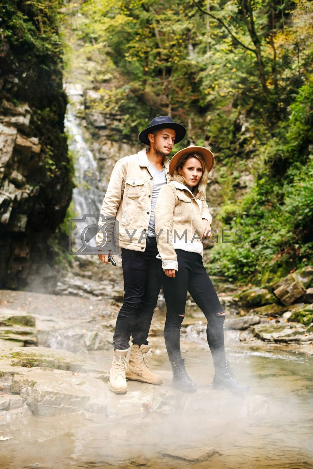 Young and beautiful couple at the mountain waterfall - Happy tourists visiting mountains. Lovestory. Tourists in hats. Military fashion
