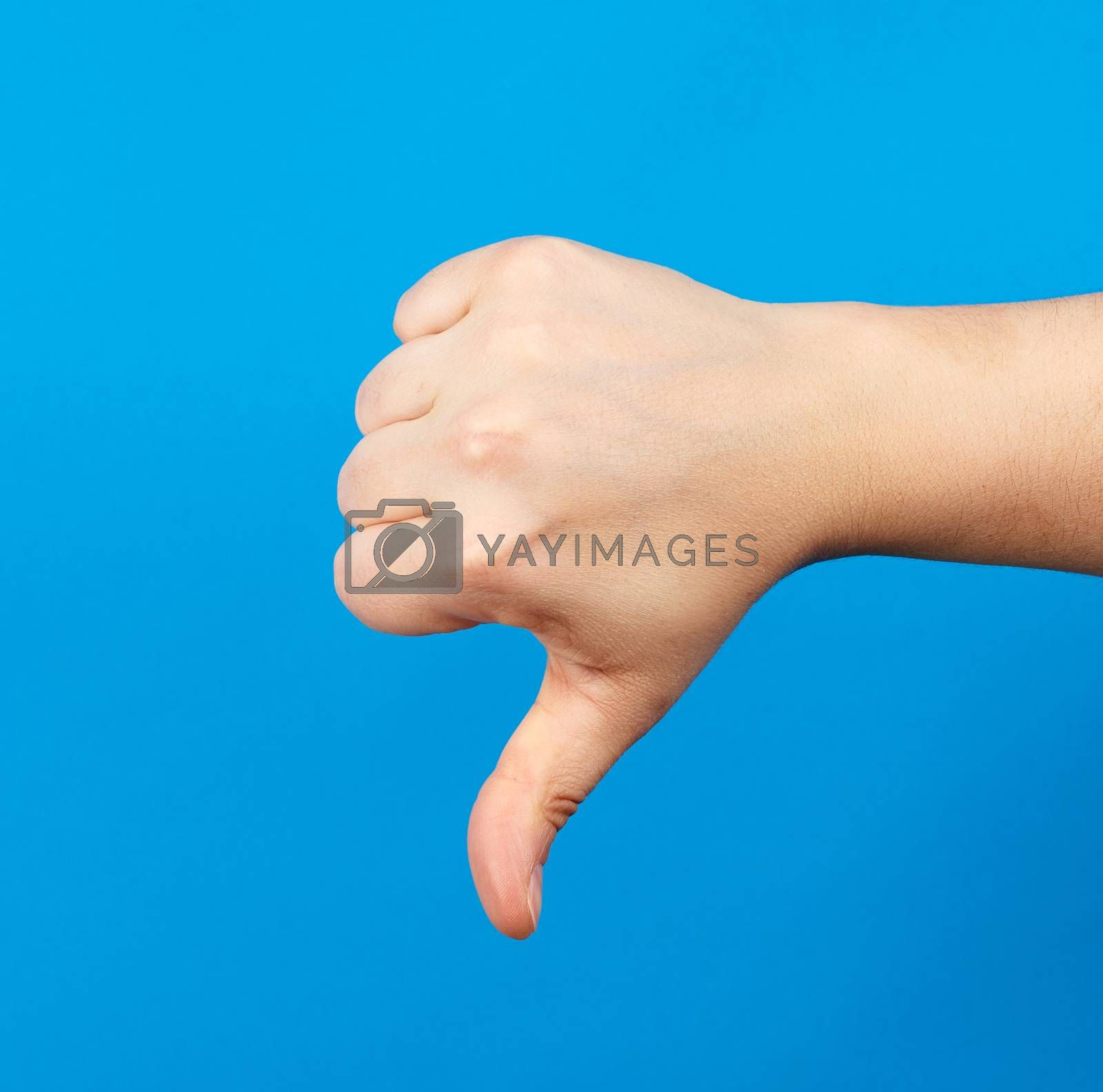 female hand shows fist gesture and thumb down, dislike, part of the body on a blue background