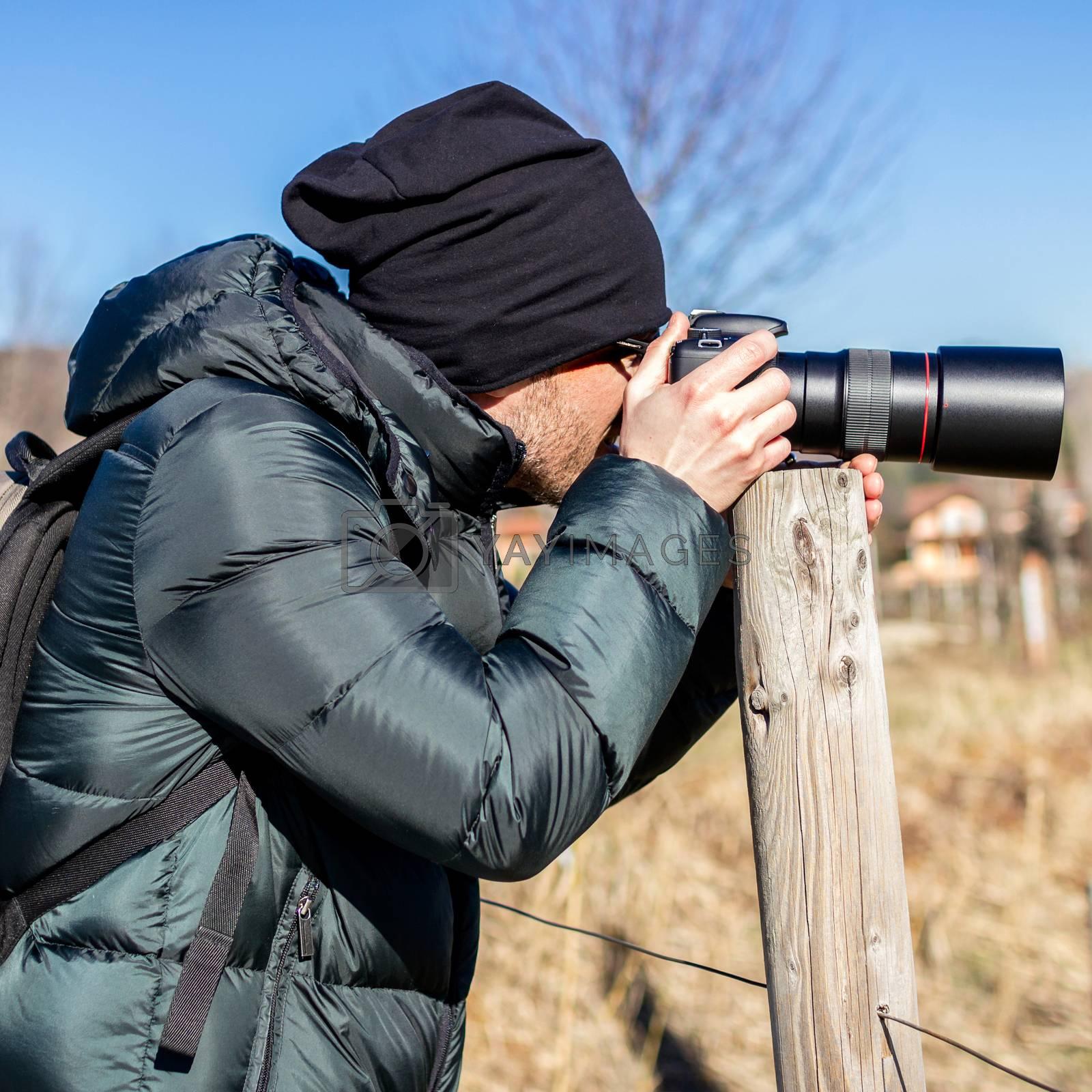 Closeup of photographer with digital camera outdoors. Young man photographer photographing nature. Shallow DOF.