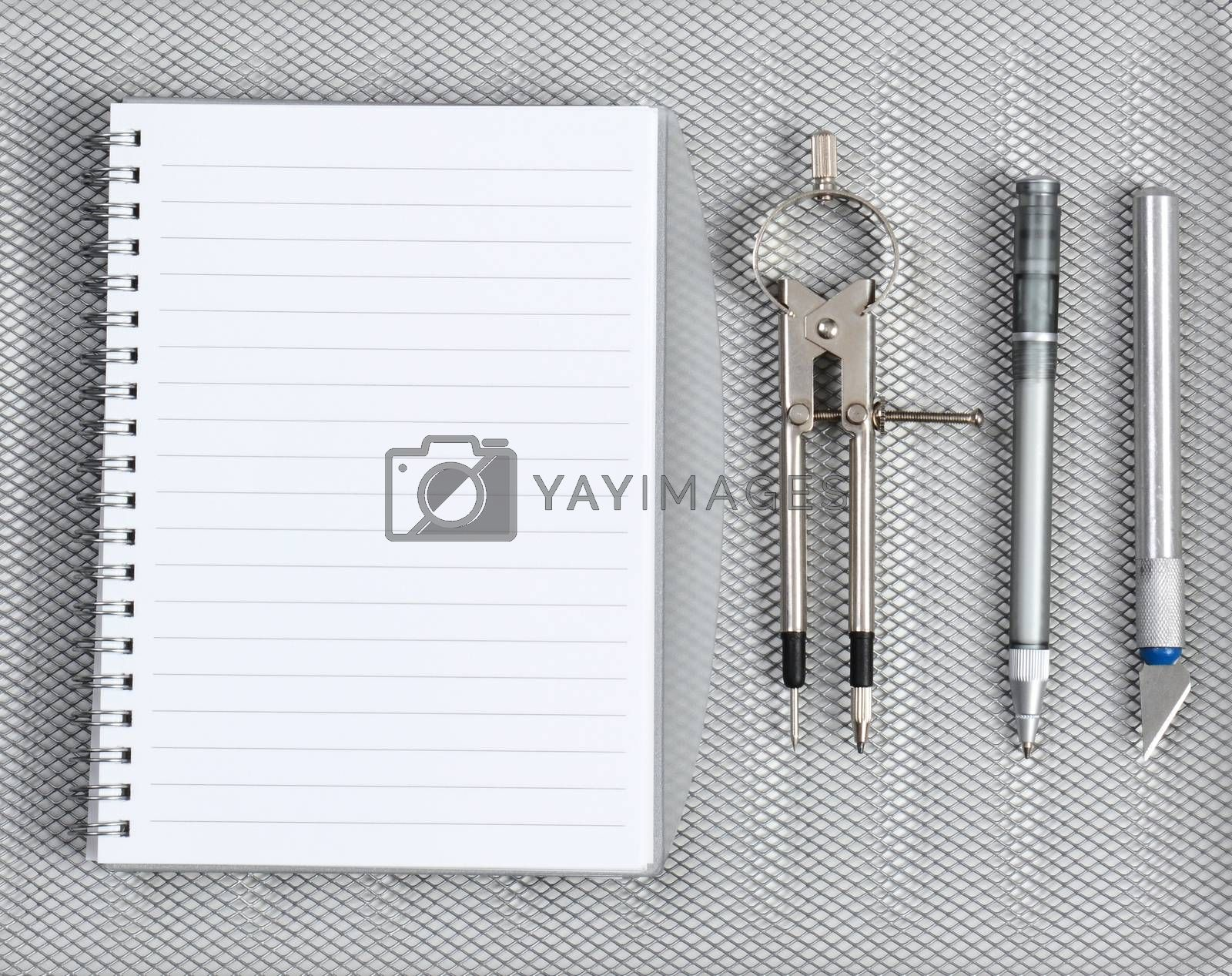 High angle shot of an open notebook with pen, compass and razor on a silver mesh background.