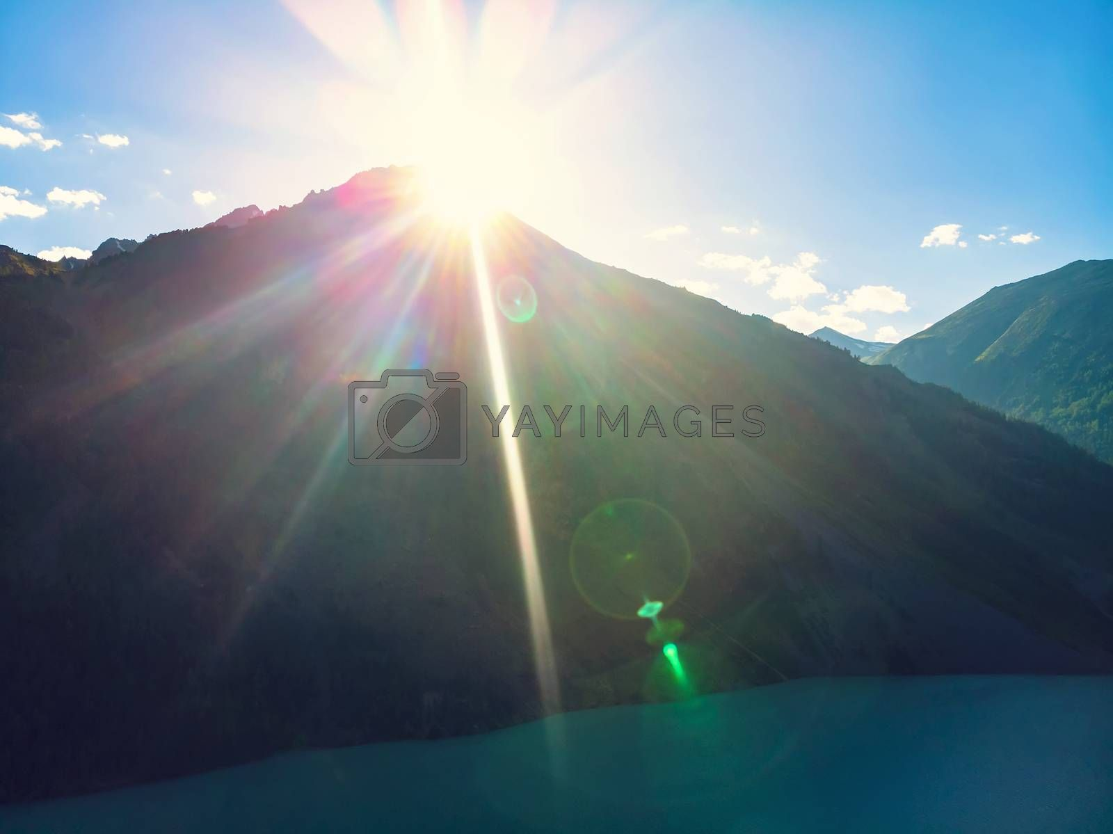 Royalty free image of Bright orange sun rays over mountain lake, Sunrise over the mountain. Bright sun rays make their way through the mountain top. by diy13