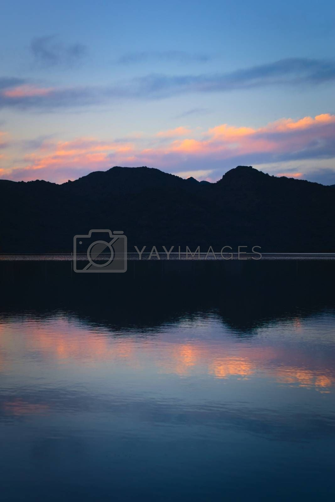 Royalty free image of Blue twilight sky and dark mountains reflected on lake by hernan_hyper