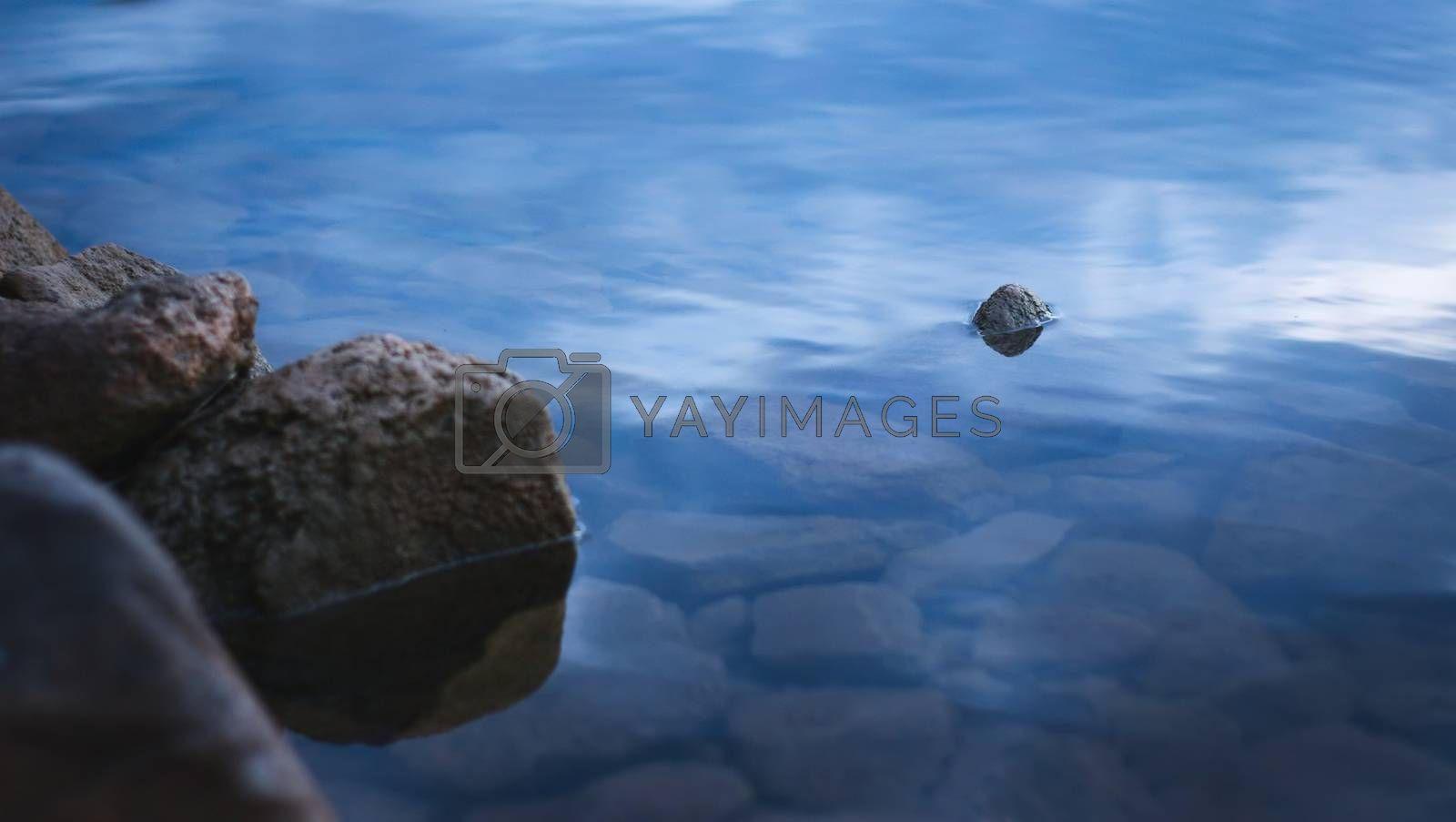 Royalty free image of Natural stones on the shore of a lake at dusk. by hernan_hyper