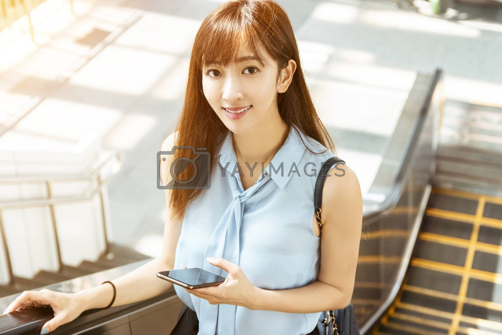 young business Woman Going To Work and holding the  mobile Phone