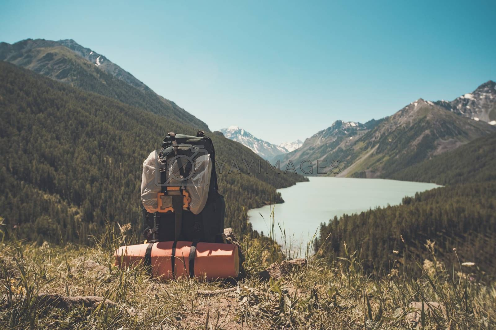 Royalty free image of touristic backpack on the riverbank. Hike concept by diy13