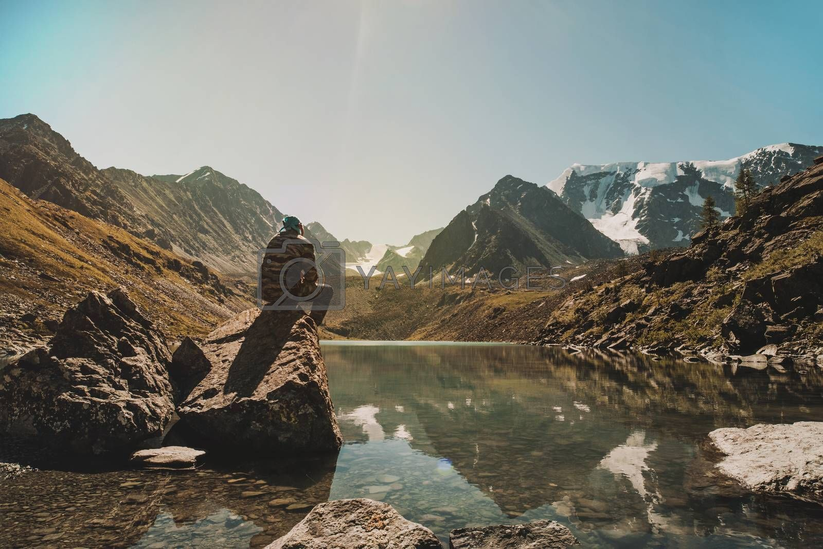 Royalty free image of Young traveler man sits on a stone and admires the beautiful mountain lake in the Altai mountains. Siberia Russia. A man in camouflage military uniform. Tourist sitting on the cliff above the lake. by diy13