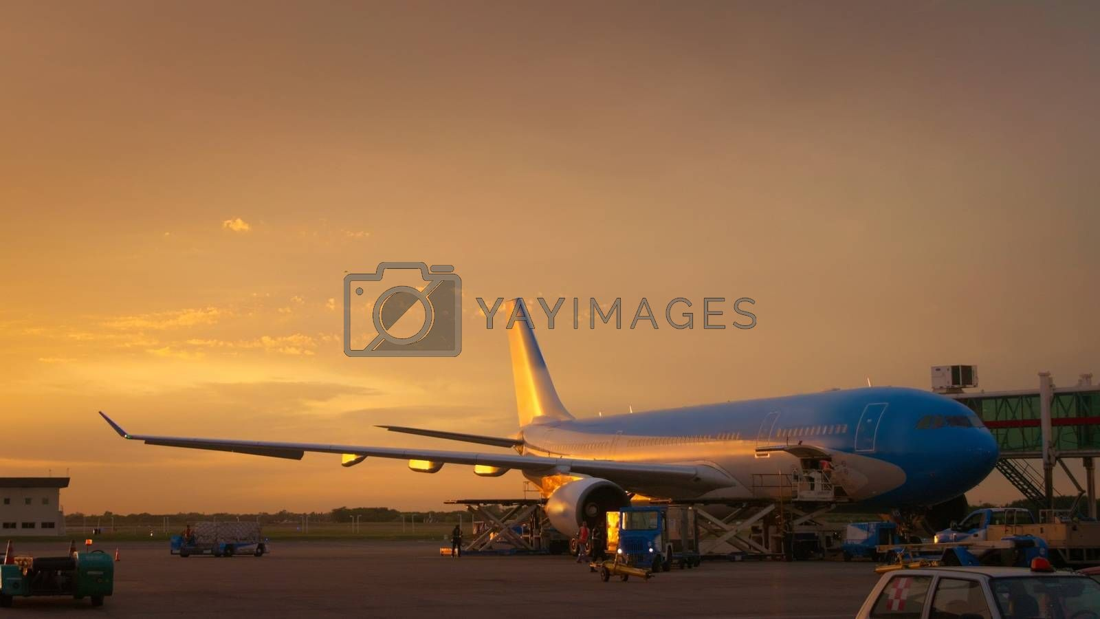 Royalty free image of Airport ground crew loading cargo and luggage on a commercial aircraft at dawn. by hernan_hyper