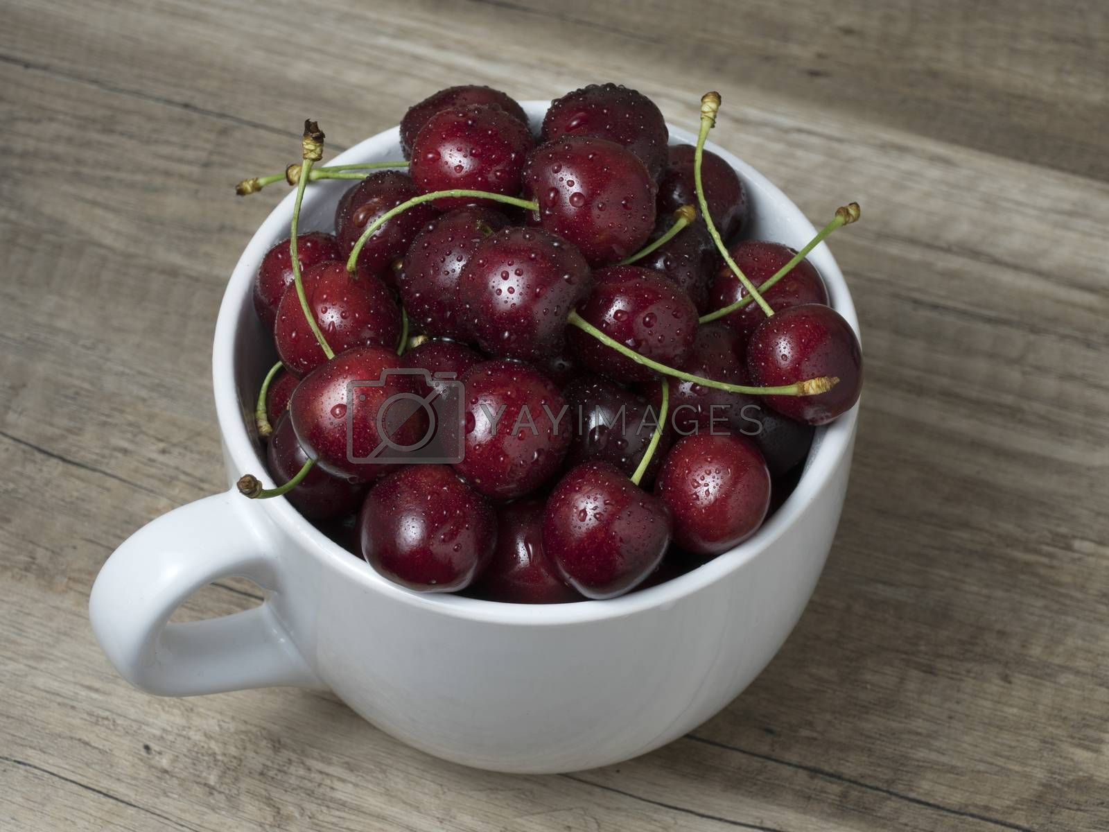 Royalty free image of Fresh ripe cherries in a cup, on wooden background.  by phortcach