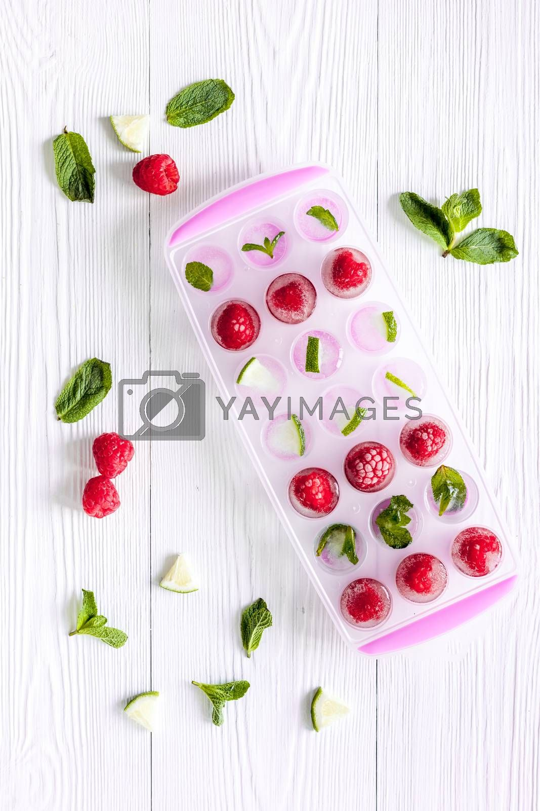 Ice tray with berries, lime and mint on background top view.