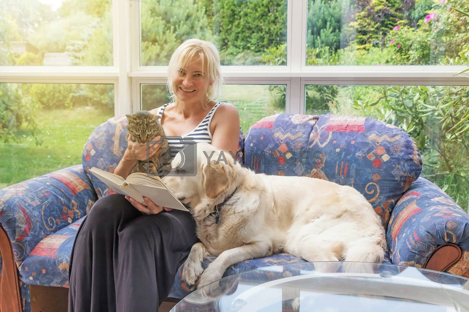 Smiling blond middle aged woman is reading a book sitting on the couch together with a cat and Golden Retriever Dog. The pets are looking at the book.