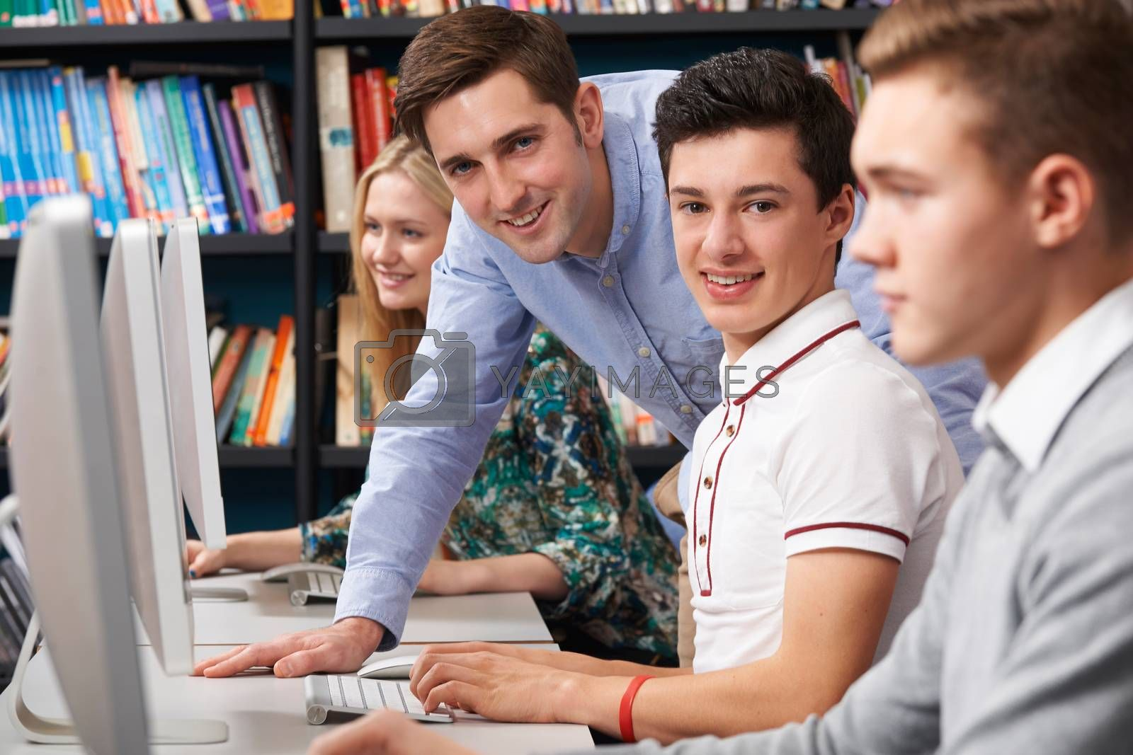 Tutor Helping Teenage Students Wotking At Computers