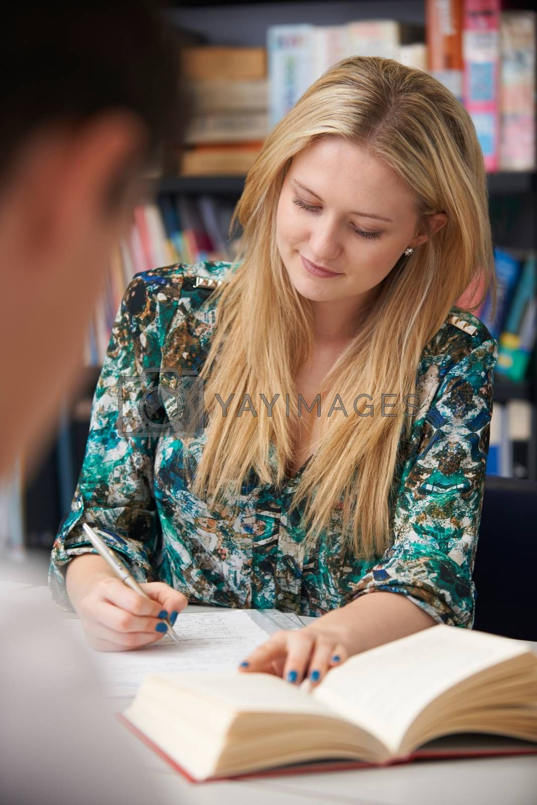 Female Student Working In Classroom