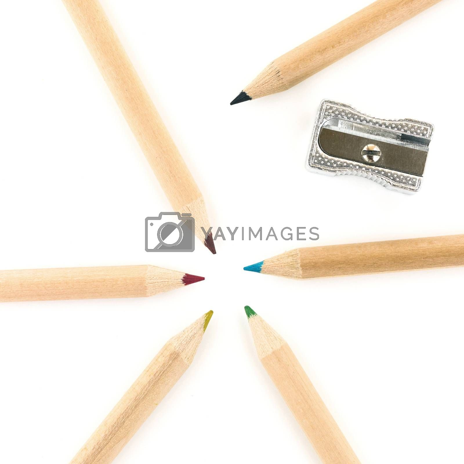 Colorful pencils and sharpener over white background