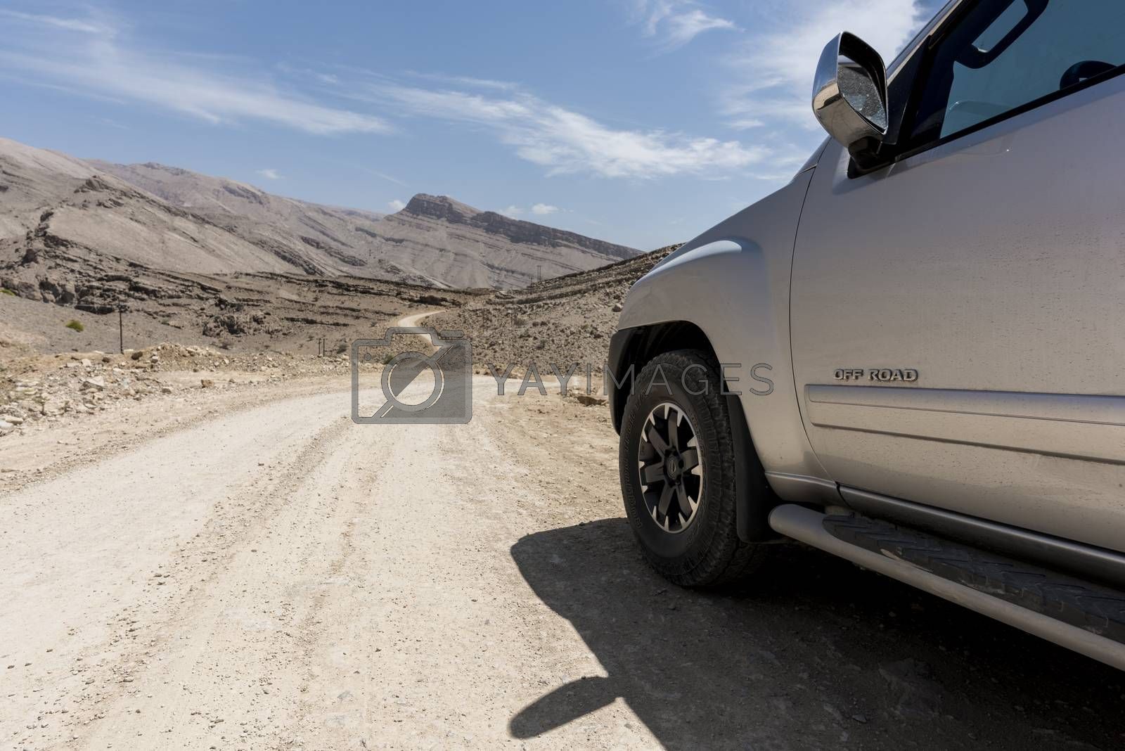 "4x4 vehicle standing on unpaved road in rocky and wild mountains of the Sultanate of Oman. We can see ""OFF_ROAD"" written on the door of the car"