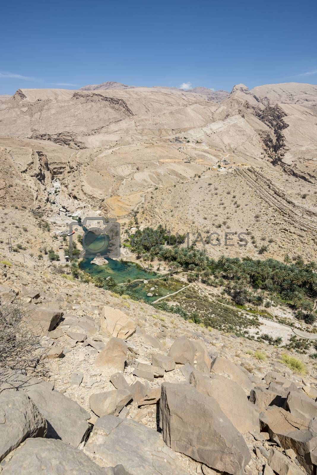 Top view of Wadi Bani Khalid, Sultanate of Oman. We can see the main pool and many tourists going and coming in/from the canyon. This is one of the most visited wadi in Oman with easy access. Many travel agencies are stopping by. It is a main destination.