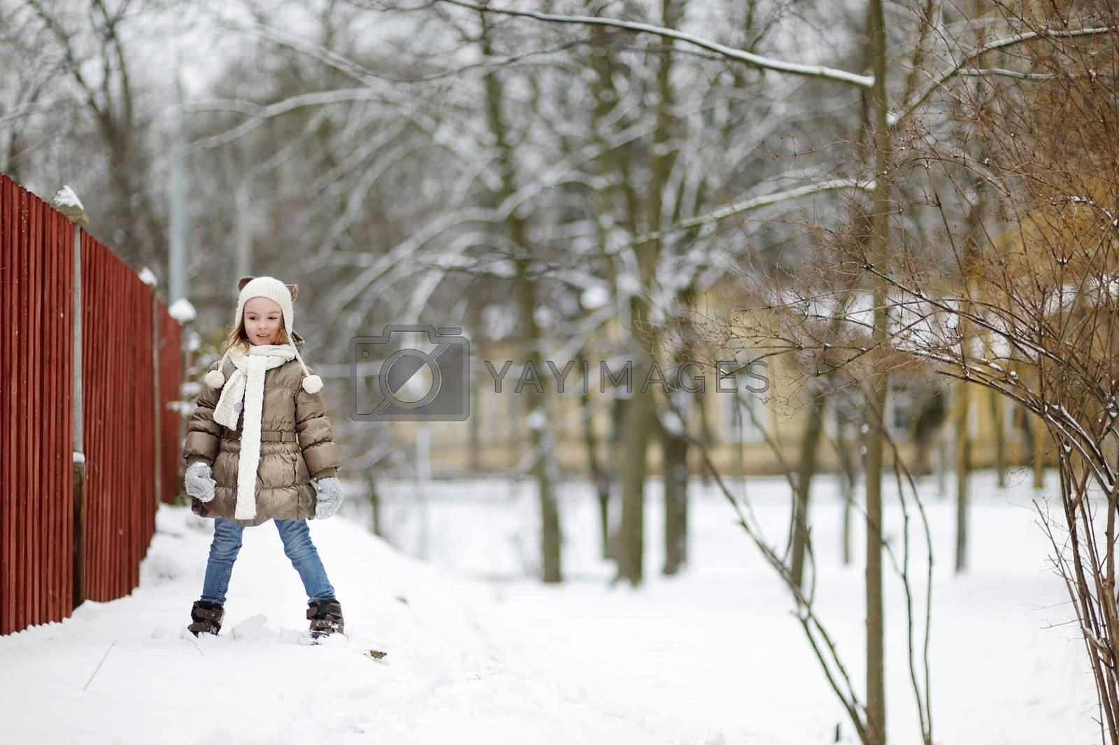 Adorable little girl having fun on beautiful winter day