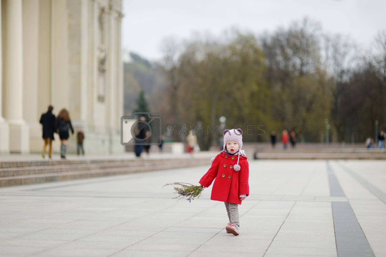 Adorable little girl holding willow branches and other plants as part of Easter tradition in Lithuania