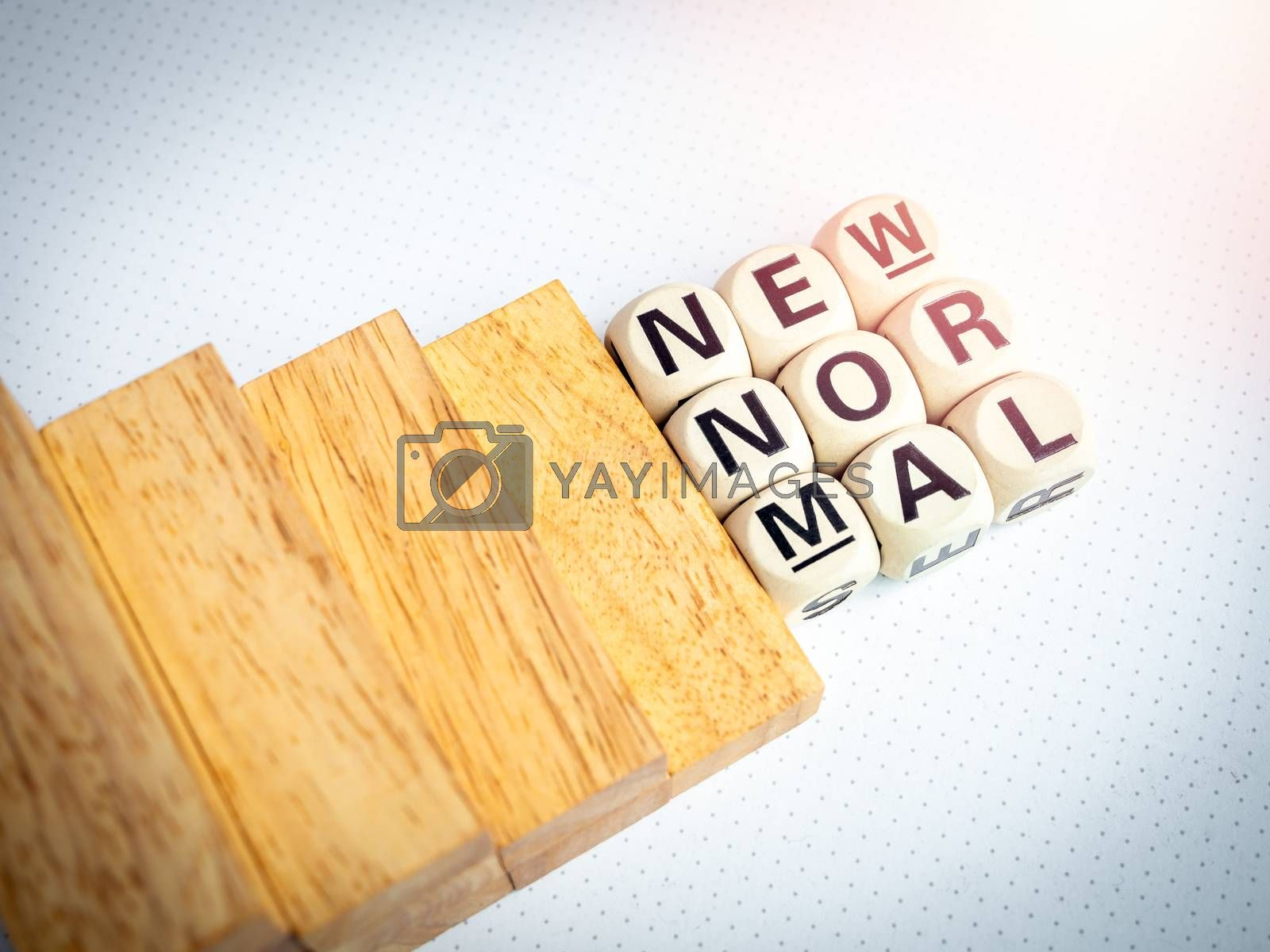Stairs down to New Normal, words on wooden alphabet cube on white background, top view. New normal after covid-19 pandemic concept.
